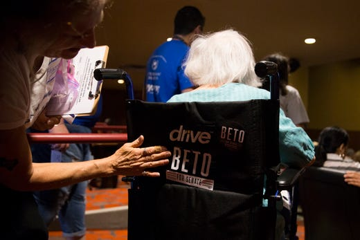 A woman attaches to a Beto O'Rourke sticker on a wheel chair during a campaign event on Saturday, Oct. 13, 2018 at Del Mar College in Corpus Christi.