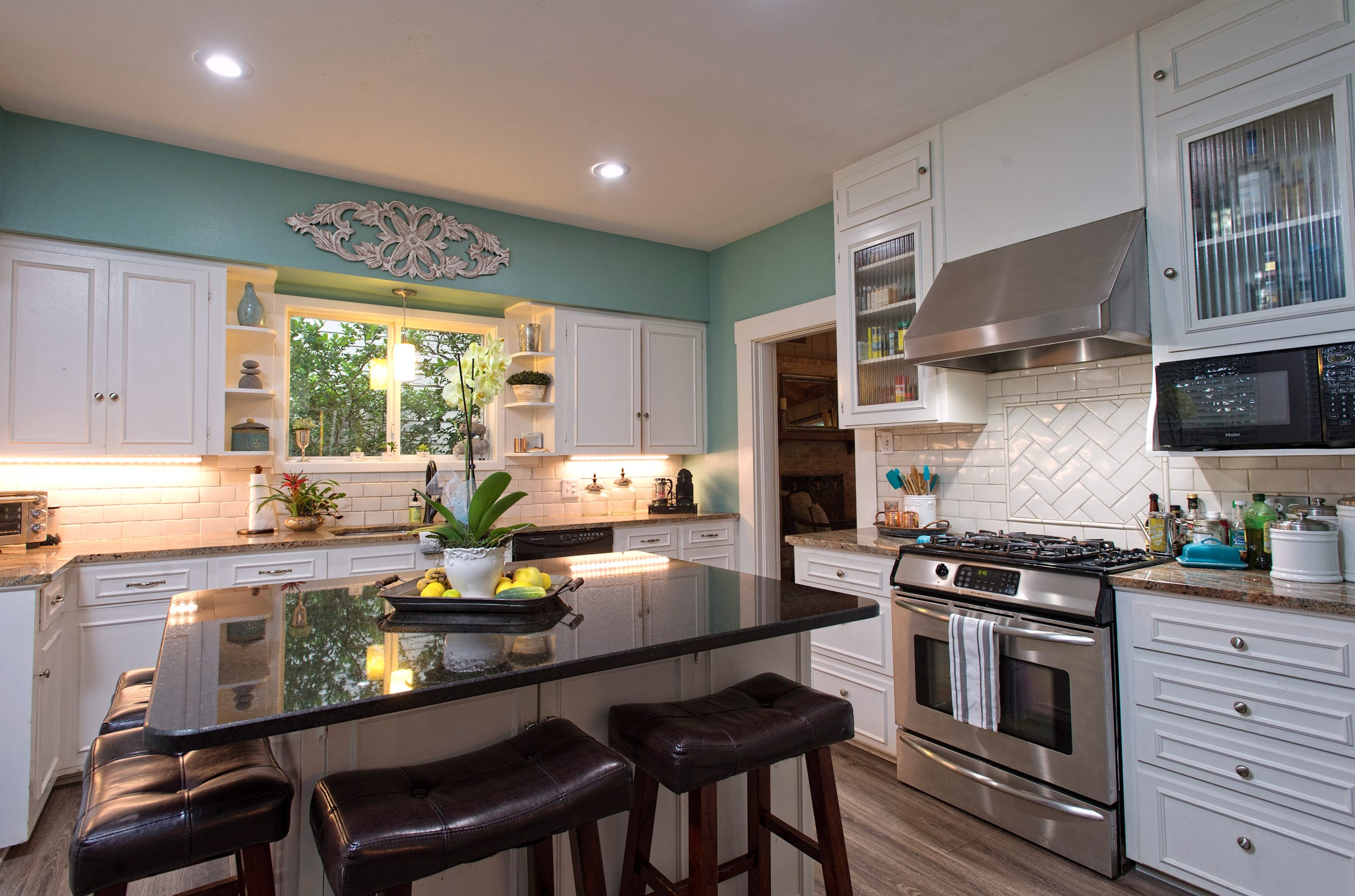 The bright and cheerful kitchen features a large granite topped island, granite counters, stainless steel appliances and custom tile and cabinetry