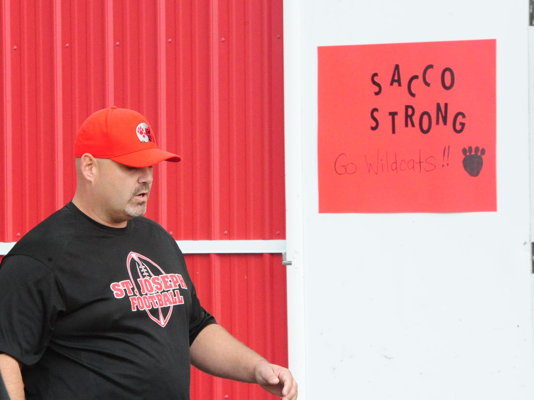 St. Joseph interim football coach Rick Mauriello walks past a sign in support of Head coach Paul Sacco before Saturday's game against West Deptford played in Hammonton on Saturday, October 13, 2018. \