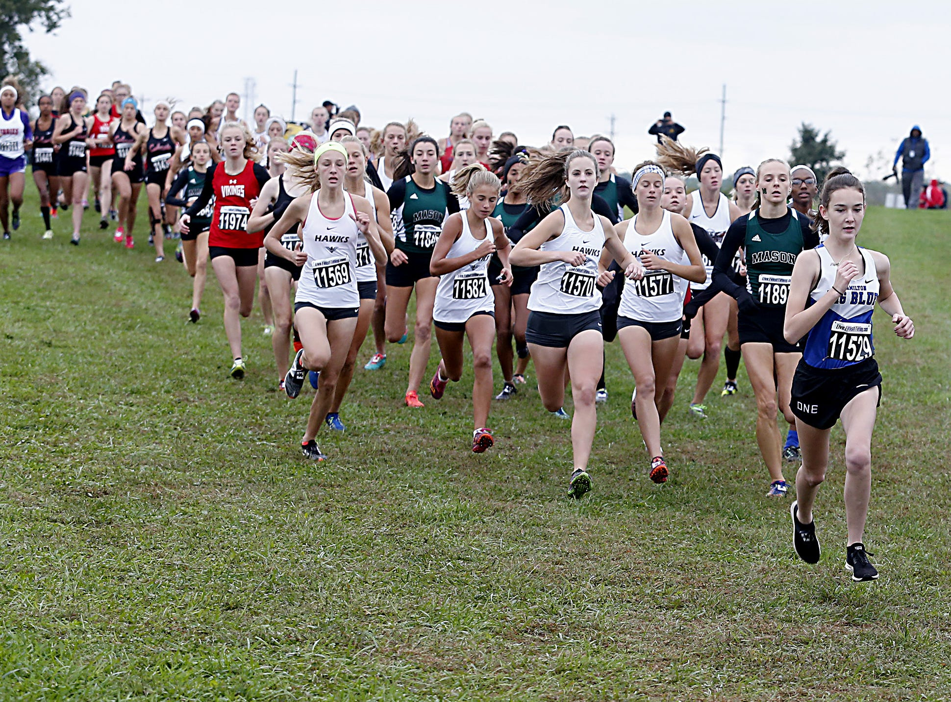Hamilton's Kinzie Ballinger leads the girls varsity race at the start during the Greater Miami Conference Girls and Boys Cross Country Championships at Voice of America Park in West Chester Saturday, Oct. 13, 2018.
