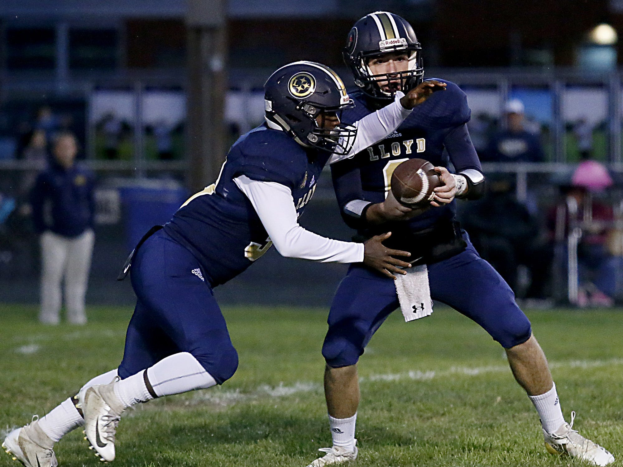 Lloyd Memorial quarterback Dakota Thiel hands off to Travon Mason during their game against Newport Central Catholic at Cecil Dees Stadium in Erlanger Friday, October 12, 2018.