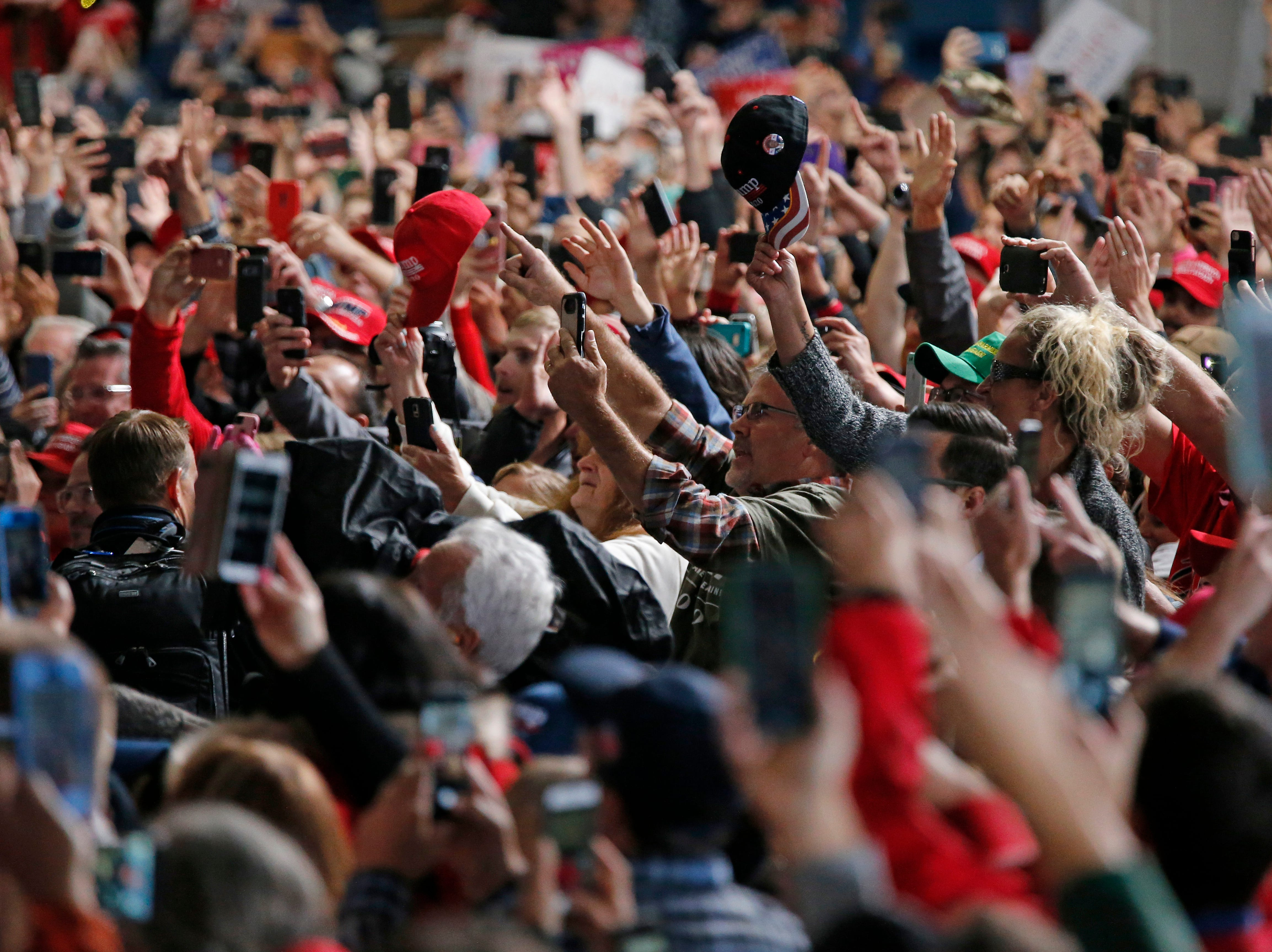Supporters raise their phones and hands as President Donald Trump takes the stage during a Make America Great Again rally at the warren County Fair Grounds in Lebanon, Ohio, on Friday, Oct. 12, 2018.