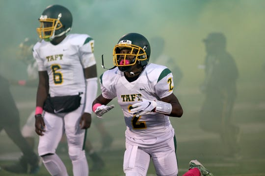Taft's Demarco Bradley Jr and the Taft Senators run on the field before the Senators' football game against  Western Hills, Friday, Oct.12,2018.