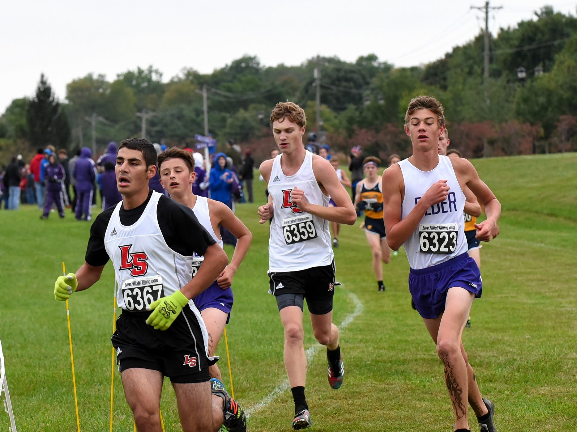 Mark Waters and Joe Marshall of La Salle join Elder's Andrew Sander taking a hard turn at the 2018 GCL/GGCL Cross Country Championships, October 13, 2018.