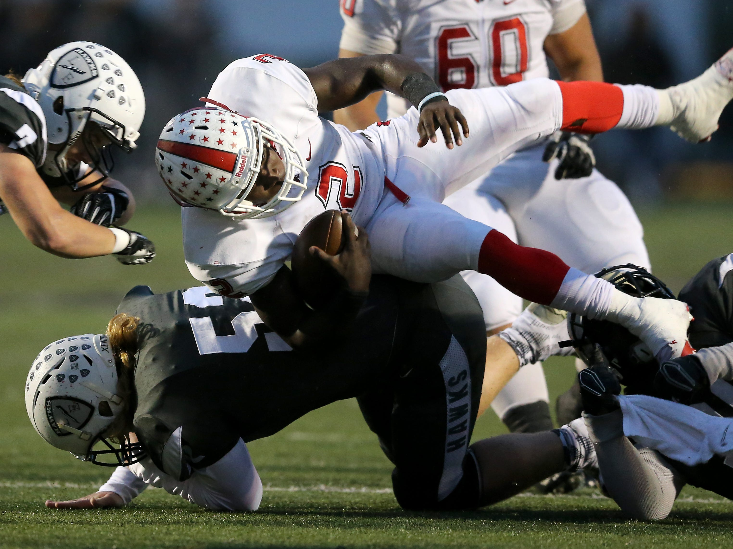 Colerain Cardinals quarterback Deante Smith-Moore (2) is tackled by Lakota East Thunderhawks defensive tackle Owen Opp (52) in the first quarter during a high school football game between the Colerain Cardinals and the Lakota East Thunderhawks, Friday, Oct. 12, 2018, at Lakota East High School in Liberty Township, Ohio.