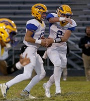 Newport Central Catholic quarterback Paul Kremer fakes a hand off to Hunter Cain during their game against Lloyd Memorial at Cecil Dees Stadium in Erlanger Friday, October 12, 2018.