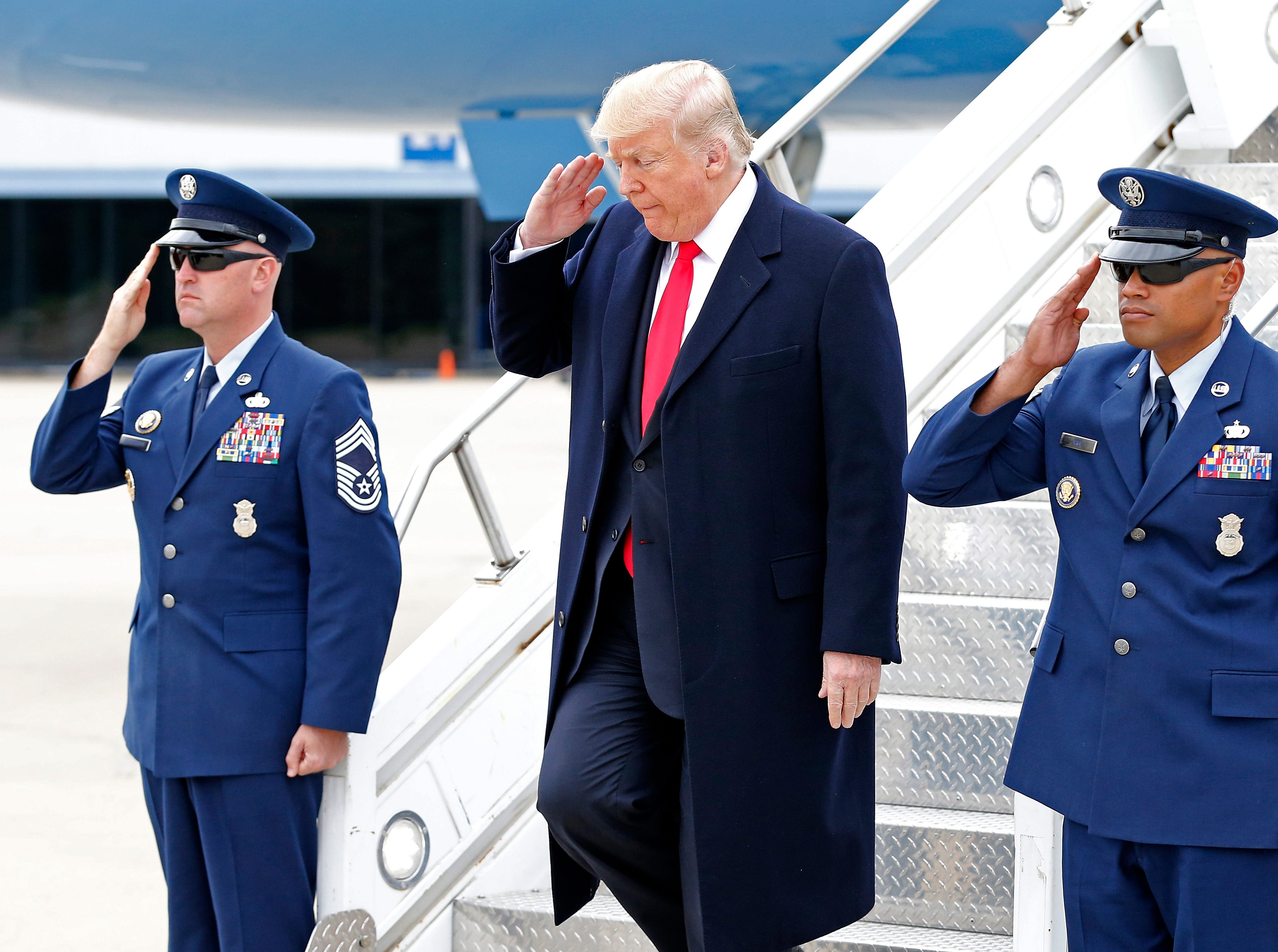 President Donald Trump salutes as he exits Air Force One after landing at Lunken Airport in Cincinnati on Friday, Oct. 12, 2018. President Trump visited the Cincinnati area for a MAGA Rally at the Warren County Fair Grounds in Lebanon, Ohio, Friday night.