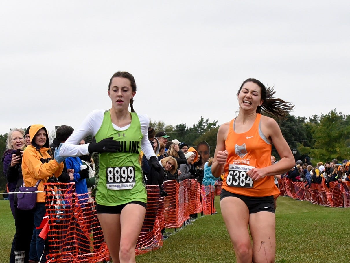 Sara Timberlake of Ursuline and Lani Hinton of Mercy McAuley run hard to the finish at the 2018 GCL/GGCL Cross Country Championships, October 13, 2018.