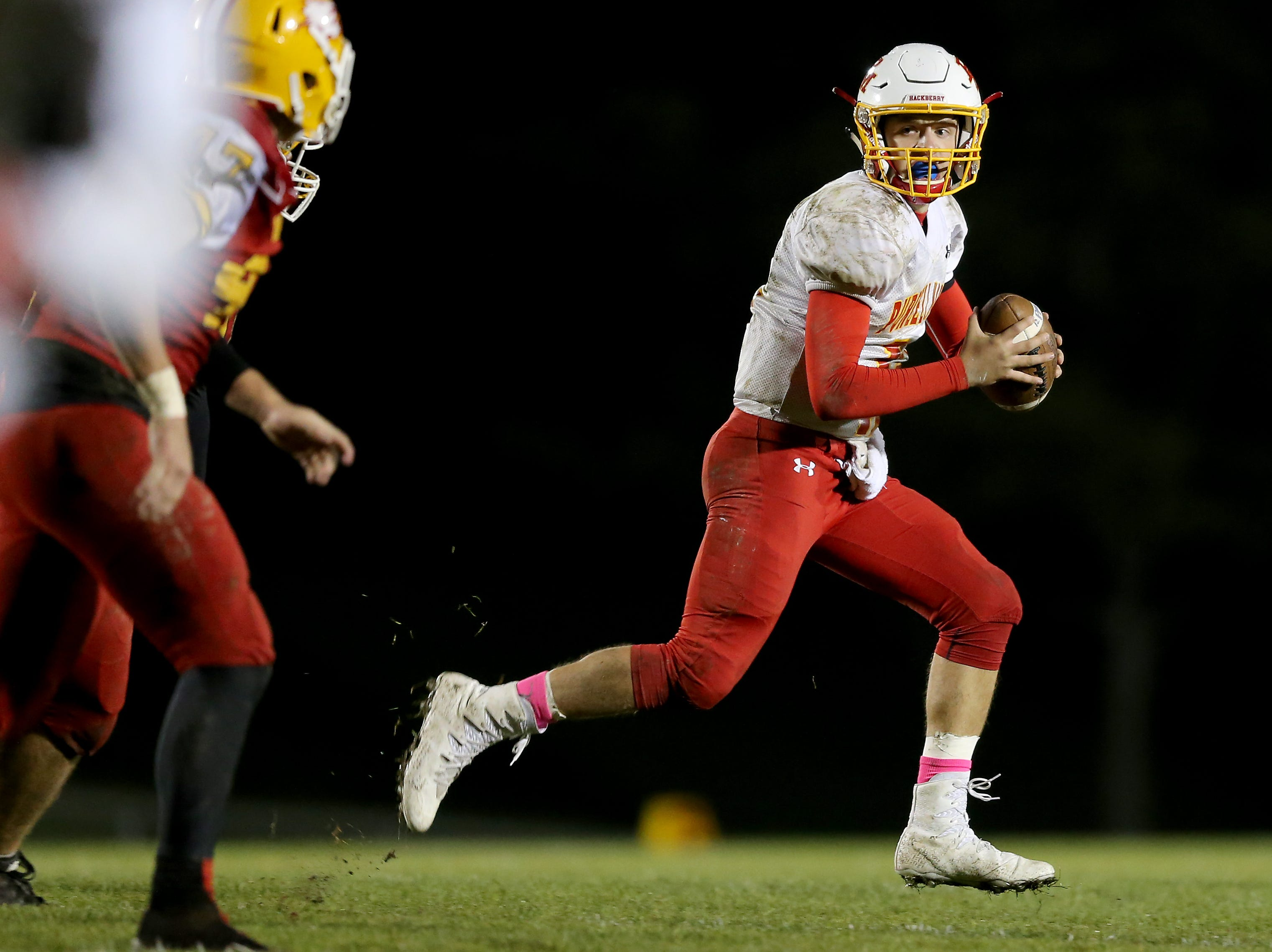 Purcell Marian quarterback Zach Hoover (12) rolls out of the pocket in the fourth quarter during a high school football game between Purcell Marian and Bishop Fenwick, Friday, Oct. 12, 2018, at Bishop Fenwick High School in Middletown, Ohio.