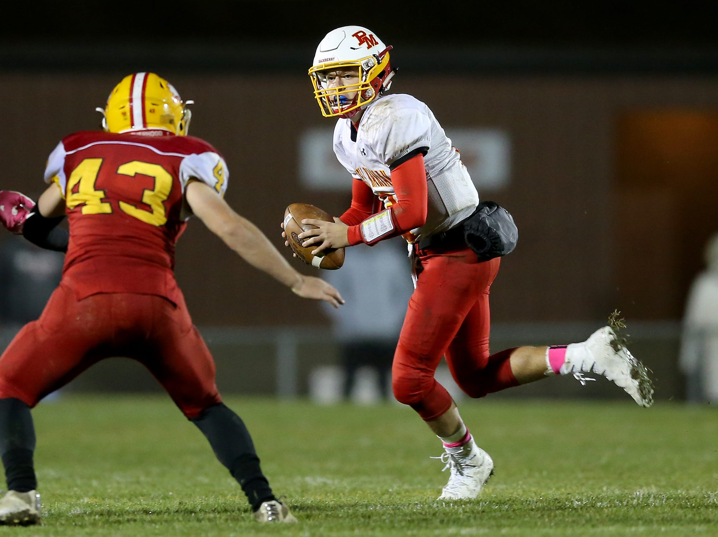 Purcell Marian quarterback Zach Hoover (12) rolls out of the pocket in the third quarter during a high school football game between Purcell Marian and Bishop Fenwick, Friday, Oct. 12, 2018, at Bishop Fenwick High School in Middletown, Ohio.