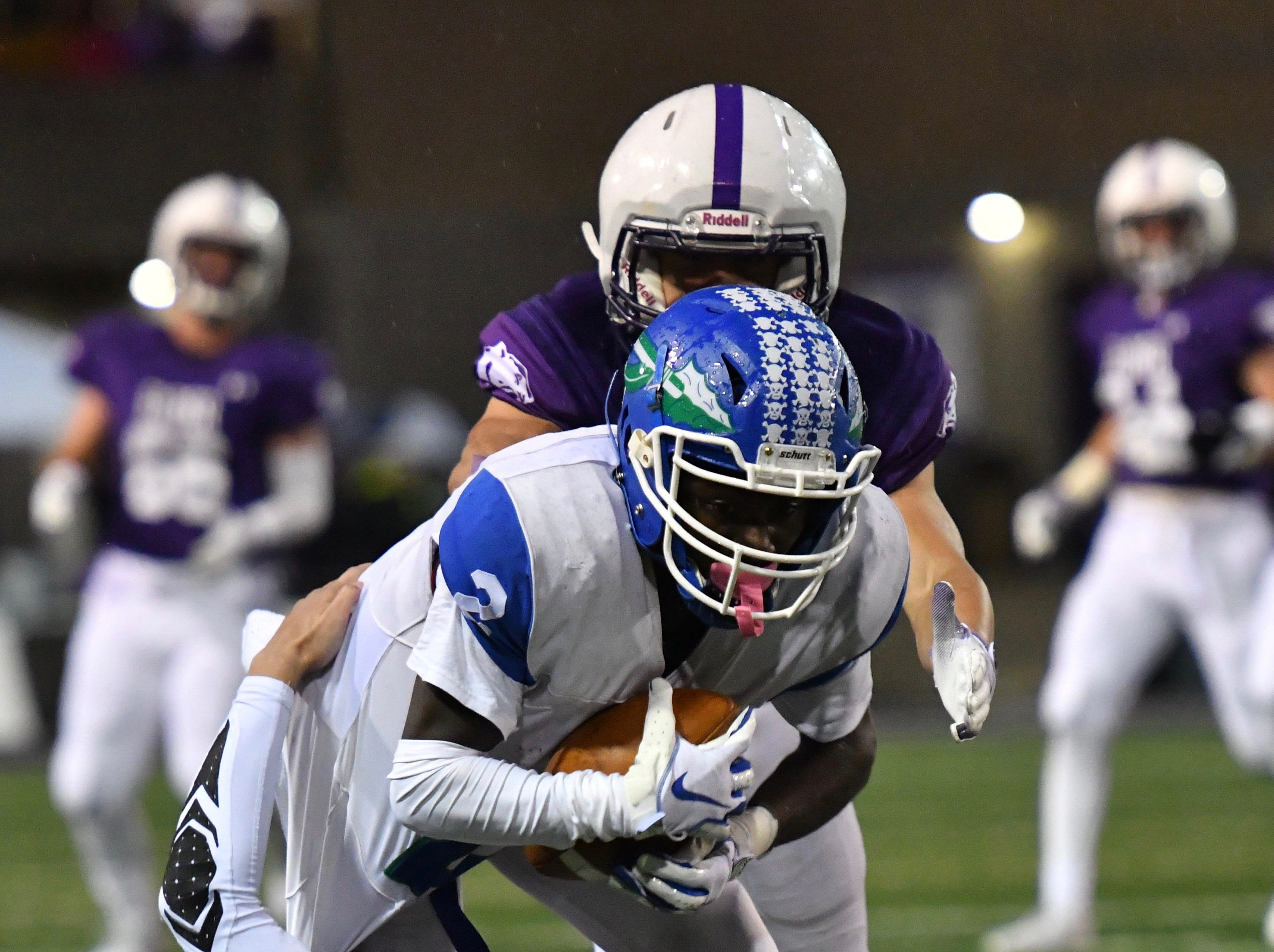 Winton Woods' Raequan Prince runs over an Elder defender for a first down Friday, Oct. 12, 2018.
