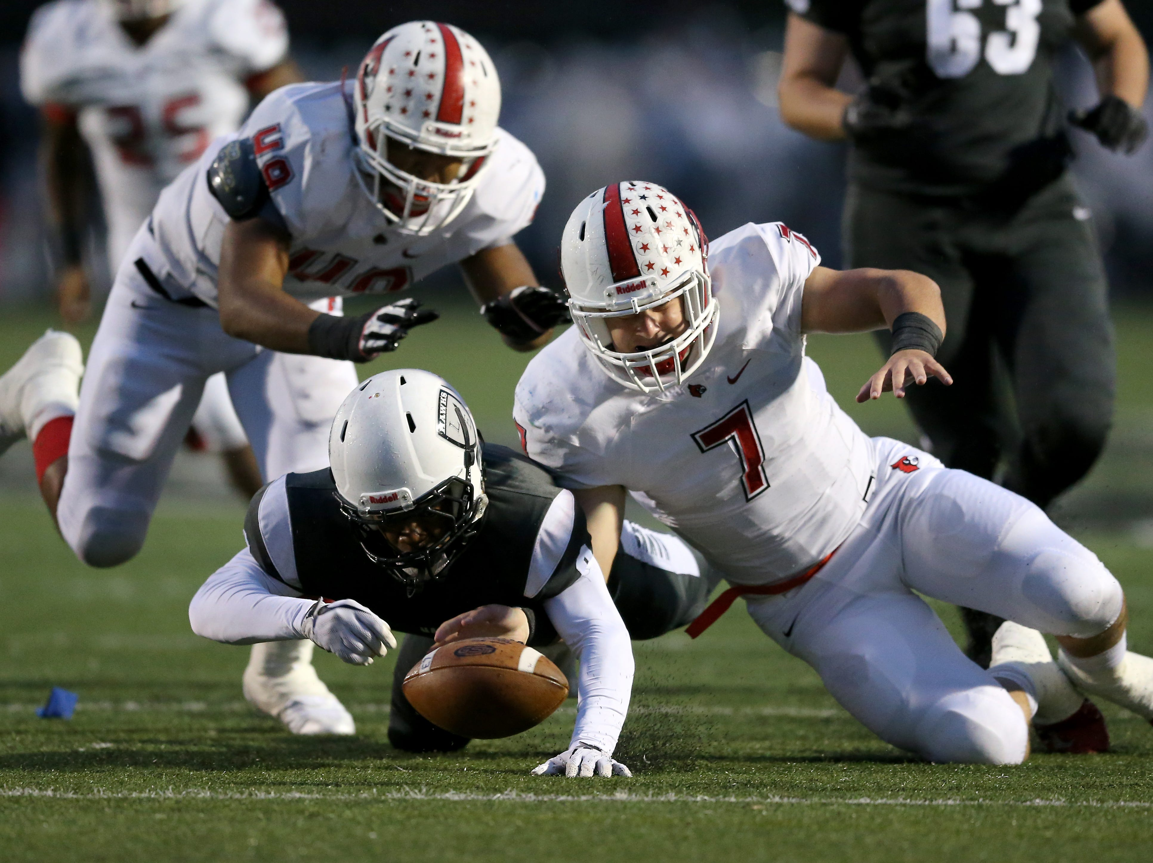 Lakota East Thunderhawks running back Donny Wilkinson (8), left, tries to recover a fumble as Colerain Cardinals linebacker Luke Bolden (7) dives for it in the first quarter during a high school football game between the Colerain Cardinals and the Lakota East Thunderhawks, Friday, Oct. 12, 2018, at Lakota East High School in Liberty Township, Ohio.