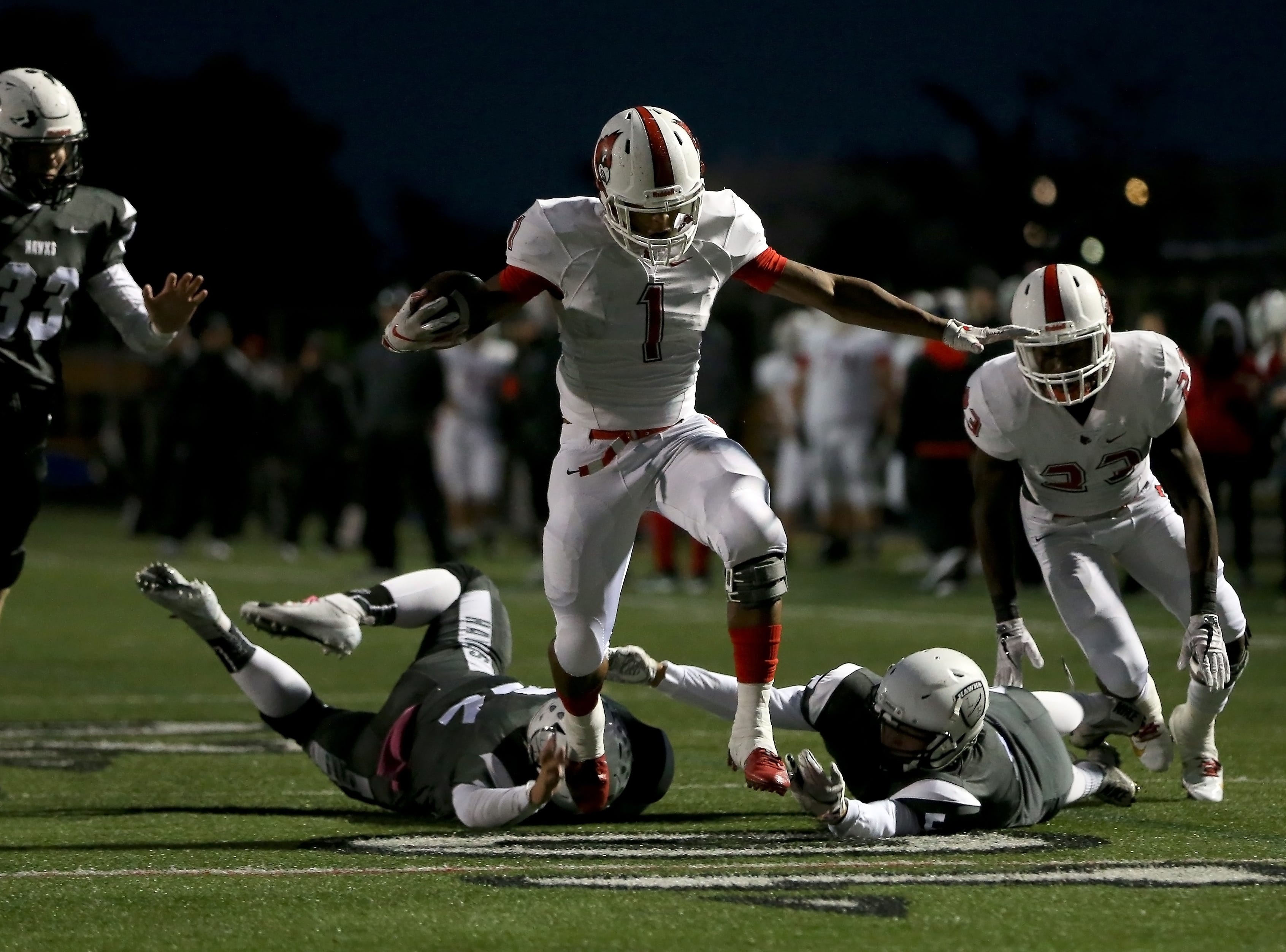 Colerain Cardinals running back Syncere Jones (1) leaps and avoids two defenders on a touchdown run in the first quarter during a high school football game between the Colerain Cardinals and the Lakota East Thunderhawks, Friday, Oct. 12, 2018, at Lakota East High School in Liberty Township, Ohio.
