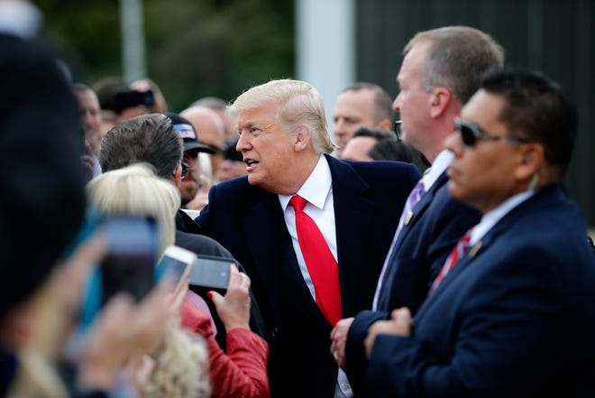 President Donald Trump greets supporters after landing at Lunken Airport in Cincinnati on Friday, Oct. 12, 2018. President Trump visited the Cincinnati area for a MAGA Rally at the Warren County Fair Grounds in Lebanon, Ohio, Friday night.