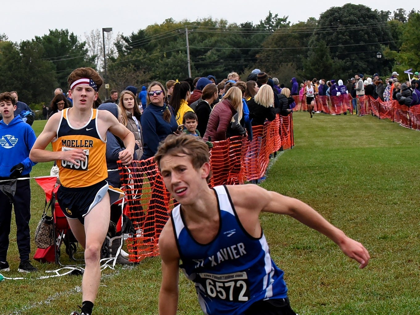 William Harmeyer of St. Xavier carries his shoe as he passes the finish at the 2018 GCL/GGCL Cross Country Championships, October 13, 2018.