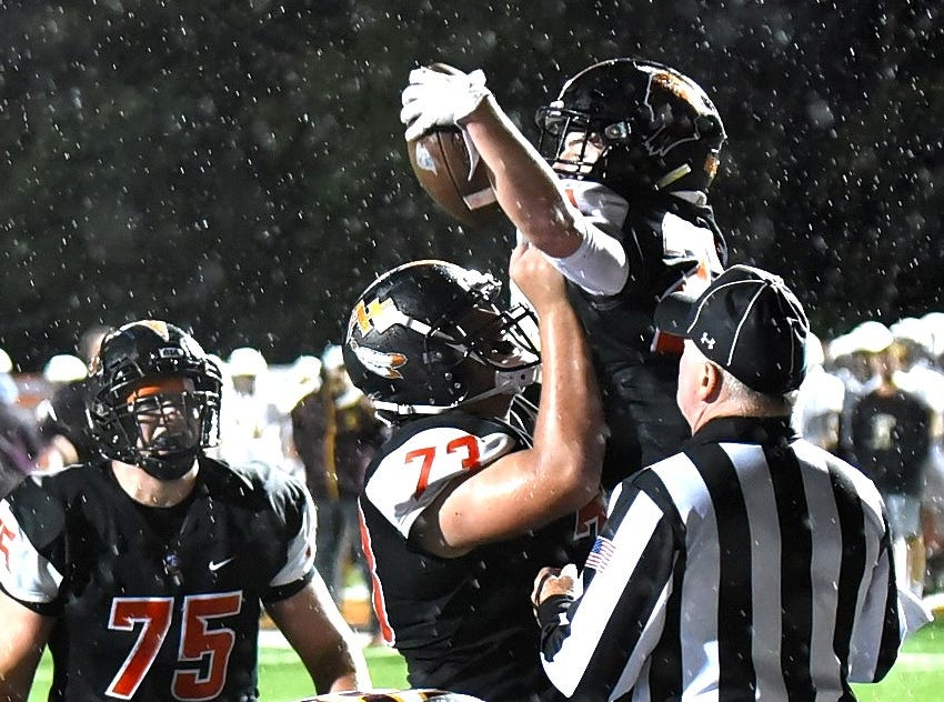 Anderson's Brian Stone (73) lifts up Owen Koelle in celebration of a Redskins' touchdown in the fourth quarter rain, October 12, 2018.