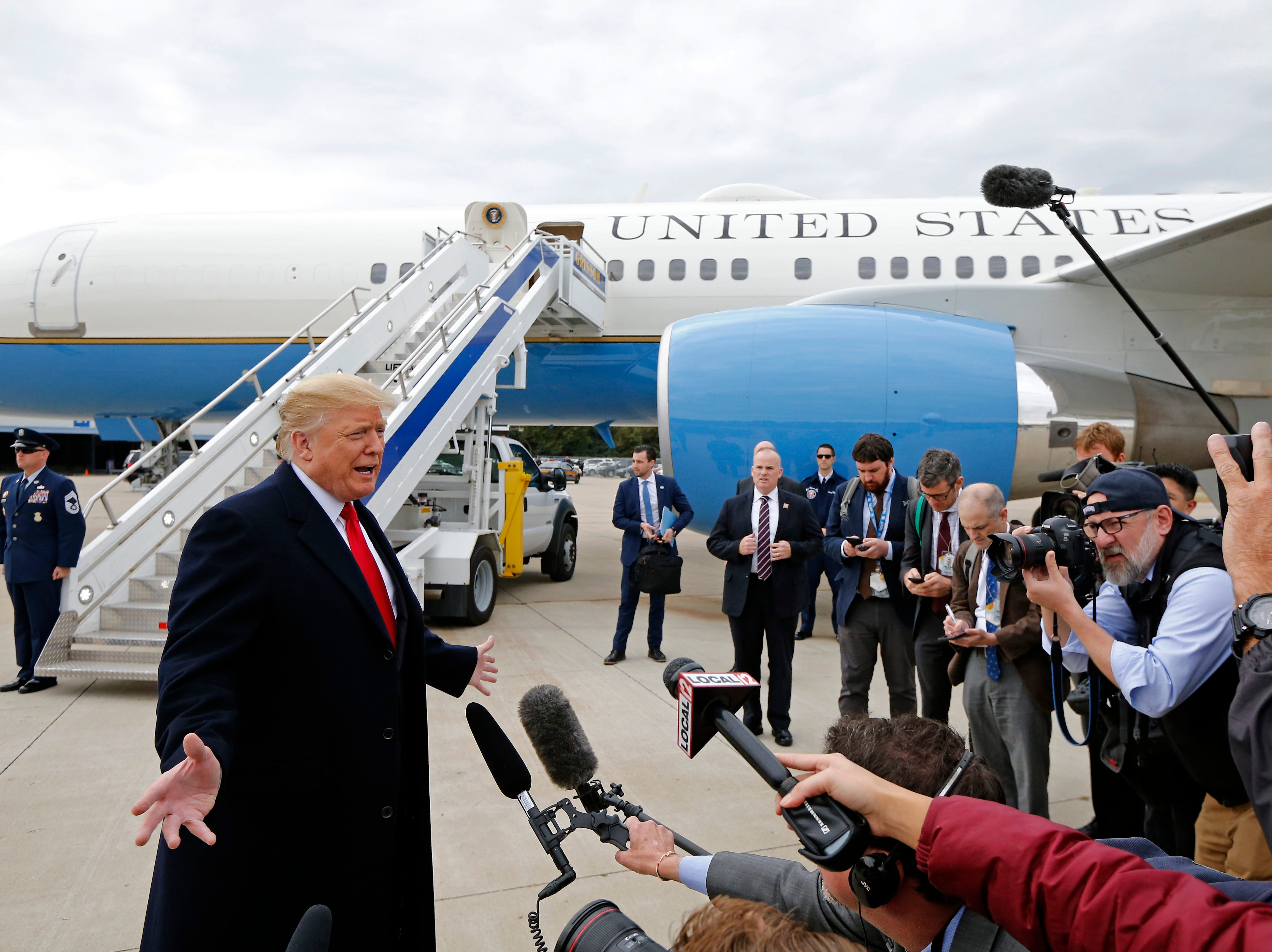 President Donald Trump takes questions from a gathering of reporters next to Air Force One at Lunken Airport in Cincinnati on Friday, Oct. 12, 2018. President Trump visited the Cincinnati area for a MAGA Rally at the Warren County Fair Grounds in Lebanon, Ohio, Friday night.