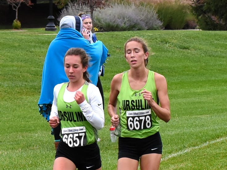 Ursuline's Hannah Doerger and Jenna Murdock run neck-n-neck on the back straightaway at the 2018 GCL/GGCL Cross Country Championships, October 13, 2018.