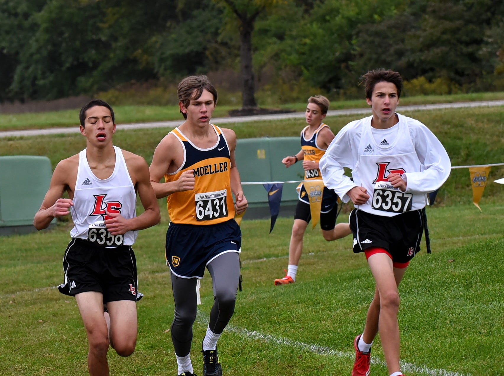 La Salle's Luke Lohman and Nicholas Lanter join Moeller's Nicholas Eiben heading out of a far turn at the 2018 GCL/GGCL Cross Country Championships, October 13, 2018.