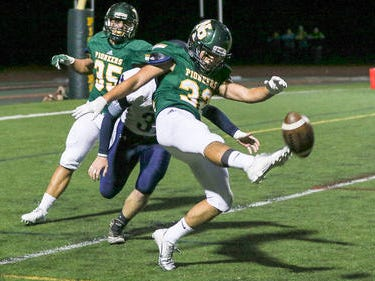 New Providence punter Jack Gertie gets the ball off under pressure from Brearley's Jonathan Braun on Friday, Oct. 12, 2018.