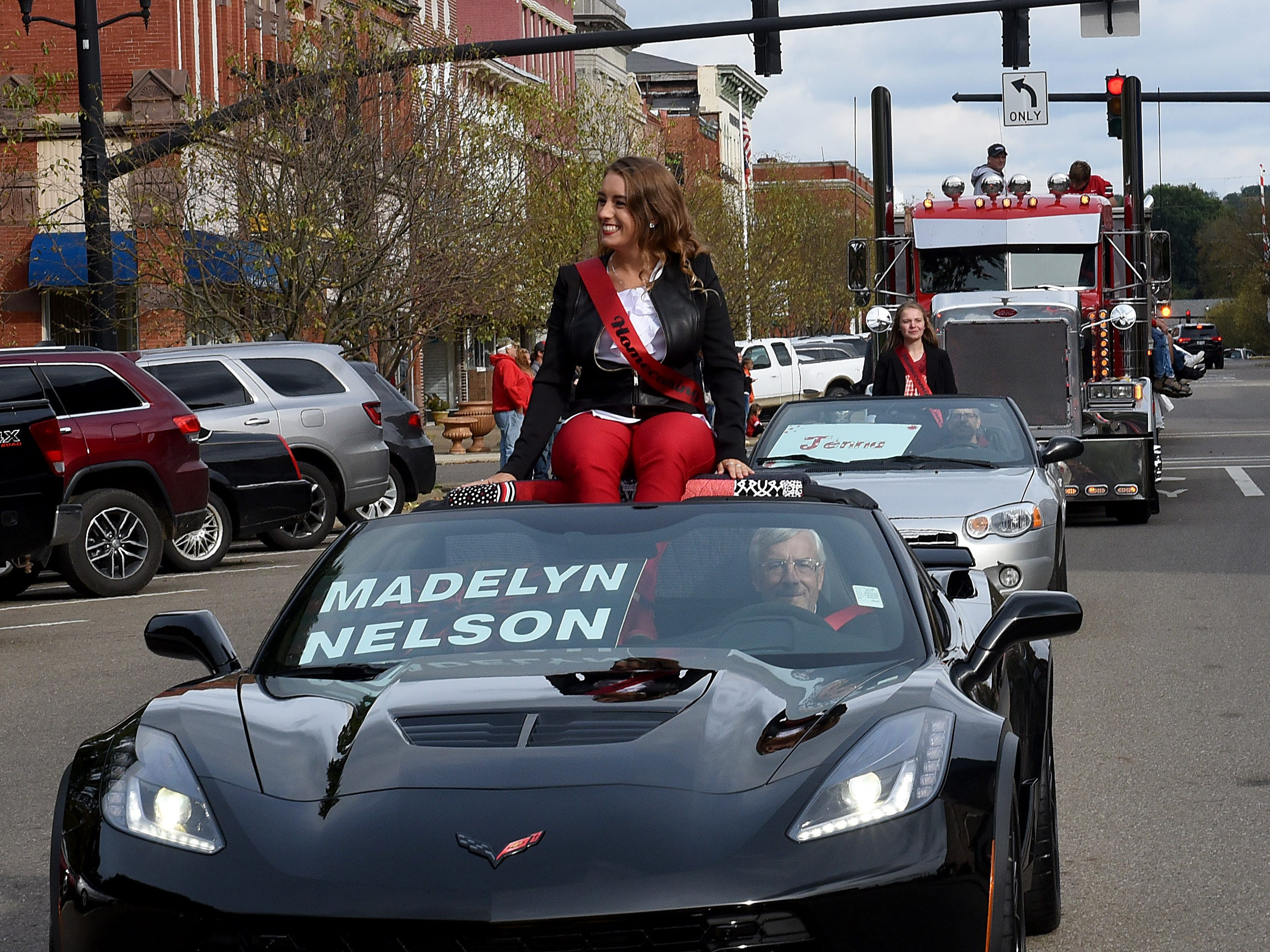 Coshocton senior and member of the homecoming court Madelyn Nelson cruises down Main Street in a convertible during the homecoming parade on Friday, Oct. 12, 2018