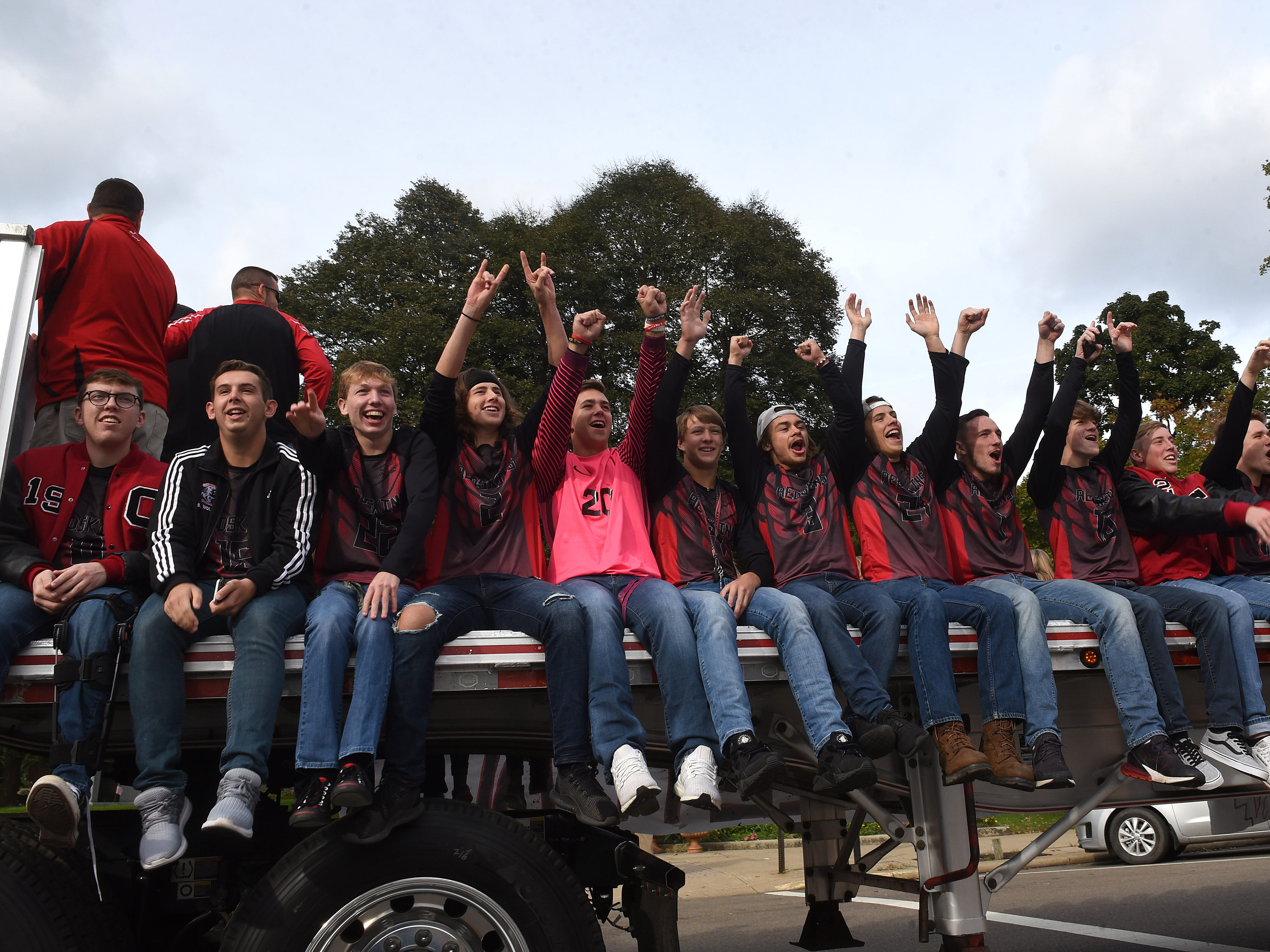 Coshocton soccer players cheer at the crowd along Main Street during the homecoming parade on Friday, Oct. 12, 2018.