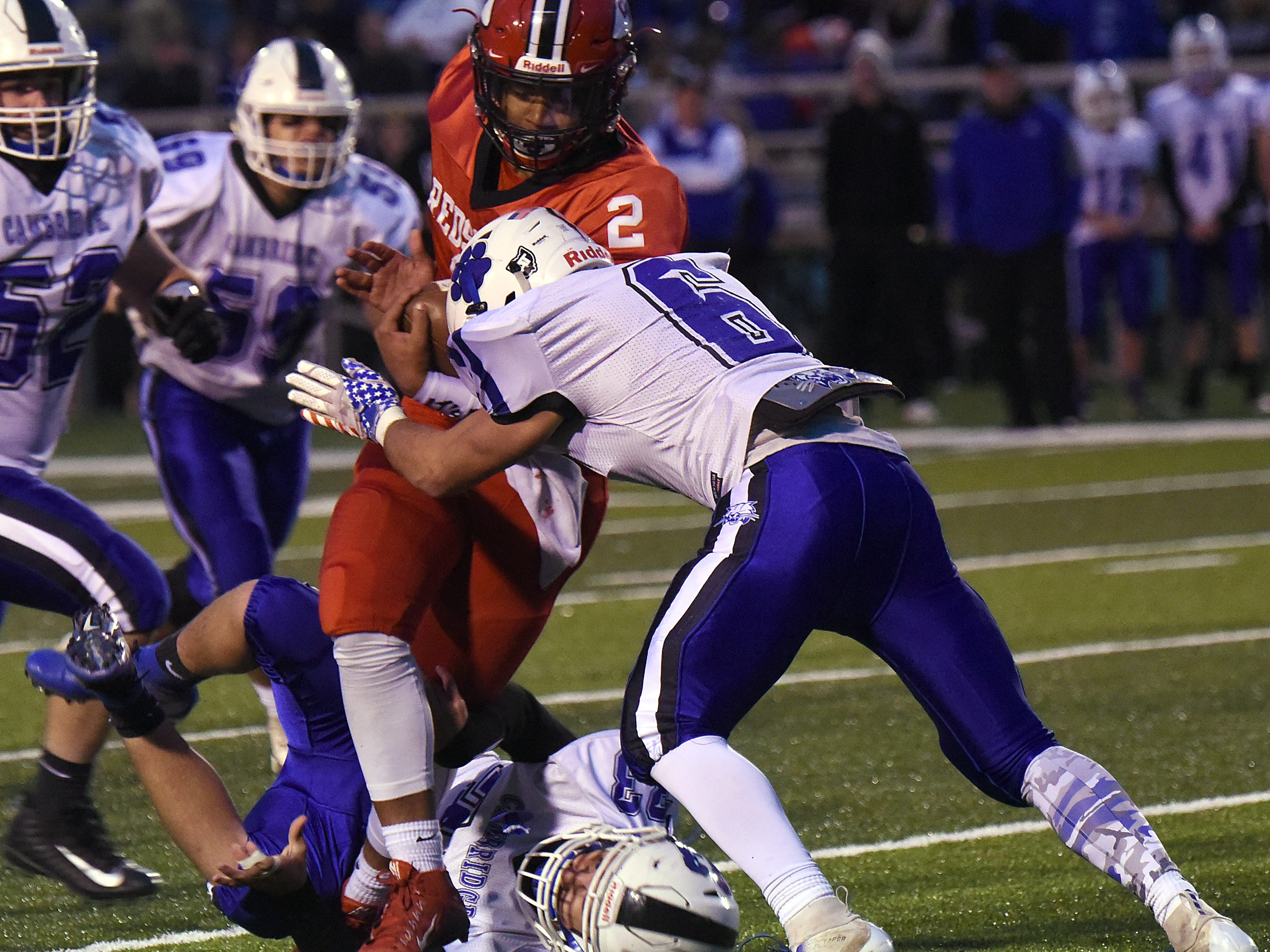 Coshocton junior Cameron Johns is brought down by Cambridge defenders Kaden Kenworthy and Logan Tuttle during their homecoming game on Friday, Oct. 12, 2018. Coshocton lost 33-22.