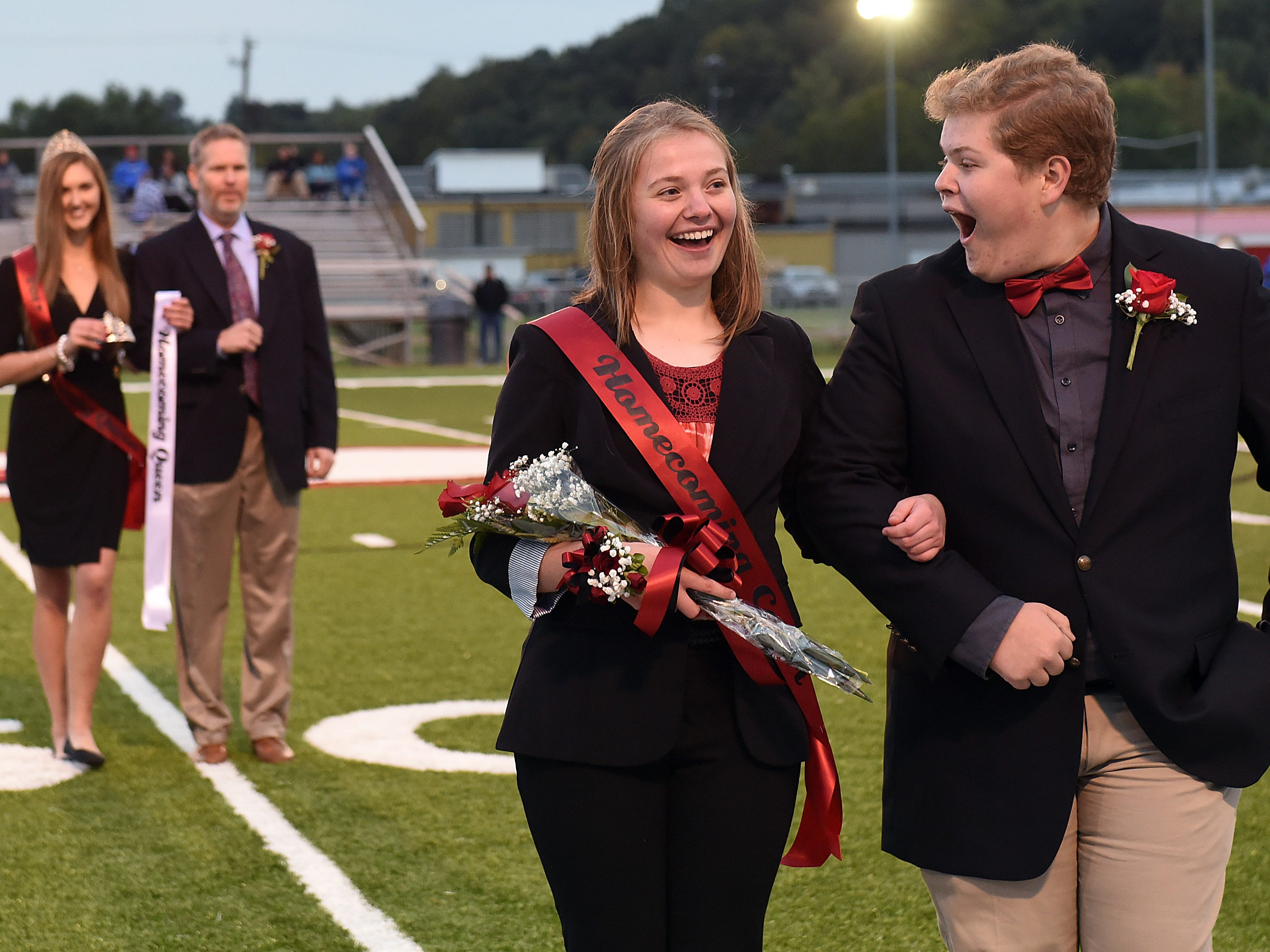 Coshocton seniors Jenna Stonebraker and Graham Beaumont react as Stonebraker is announced as the 2018 homecoming queen on the field before the start of Friday night's game against Cambridge.