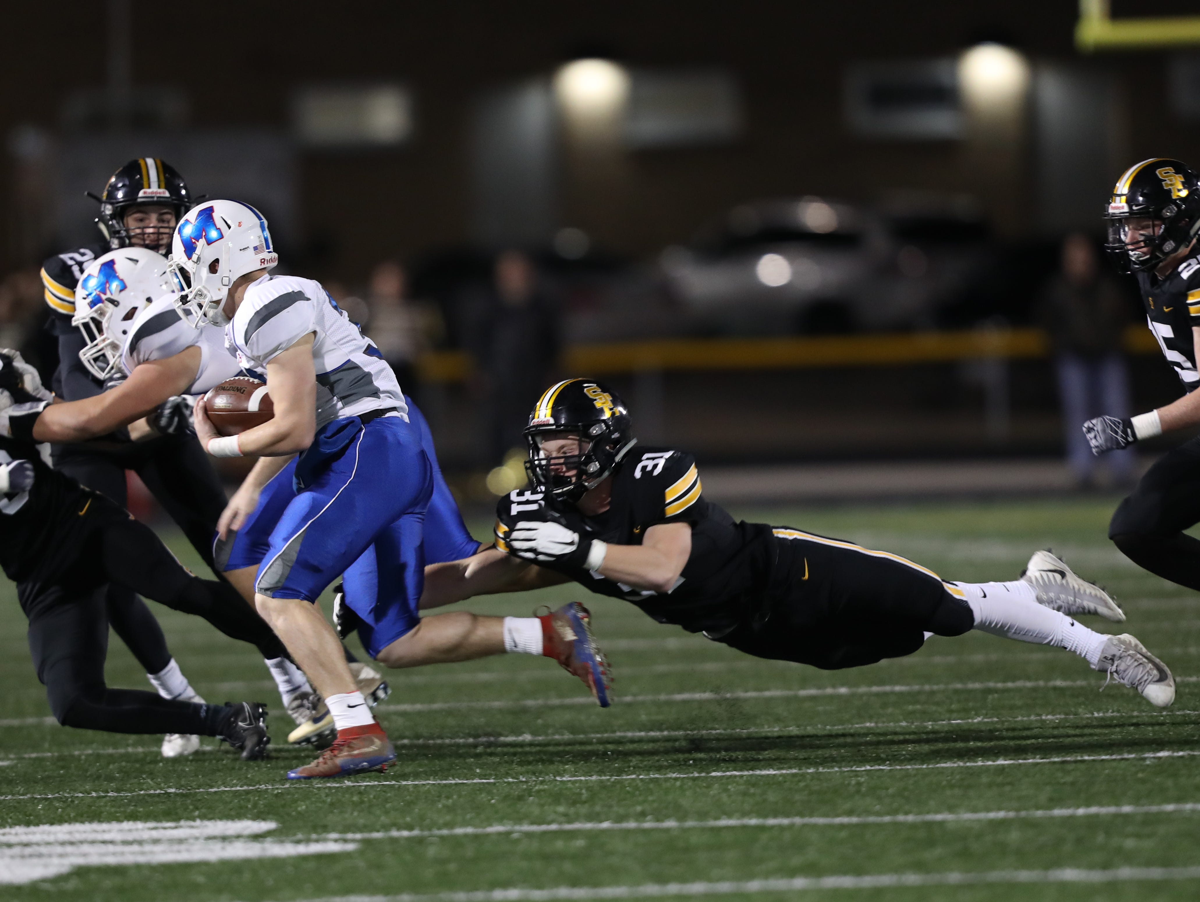 Southeast Polk Rams Carter Olesen (31) dives for a tackle against the Marshalltown Bobcats at SE Polk Stadium. The Rams beat the Bobcats 56 to 7.