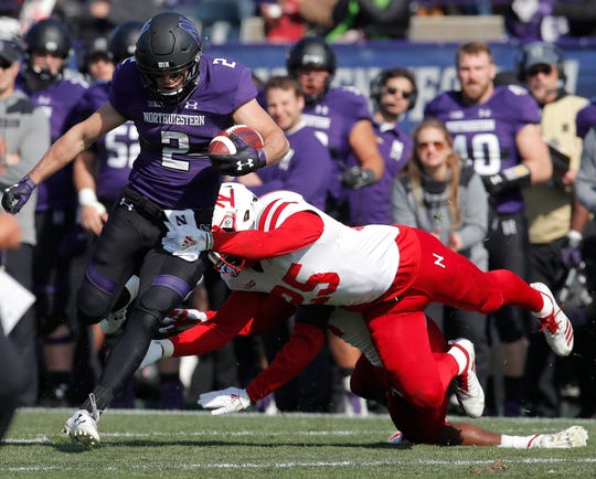 Northwestern's Flynn Nagel, left, tries to break a tackle by Nebraska's Antonio Reed during the second half.