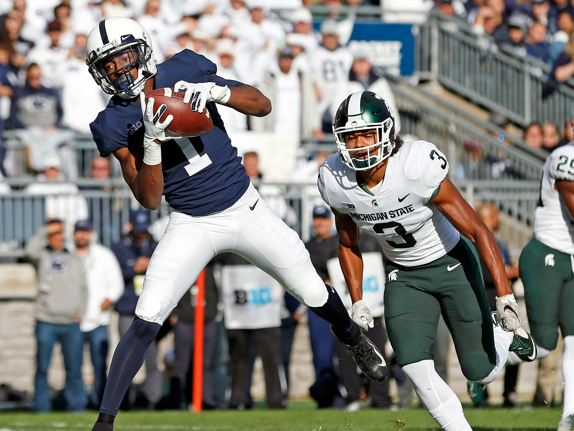 Penn State's KJ Hamler (1) catches a touchdown pass in front of Michigan State's Xavier Henderson (3) during the first half of an NCAA college football game in State College, Pa., Saturday, Oct. 13, 2018. (AP Photo/Chris Knight)