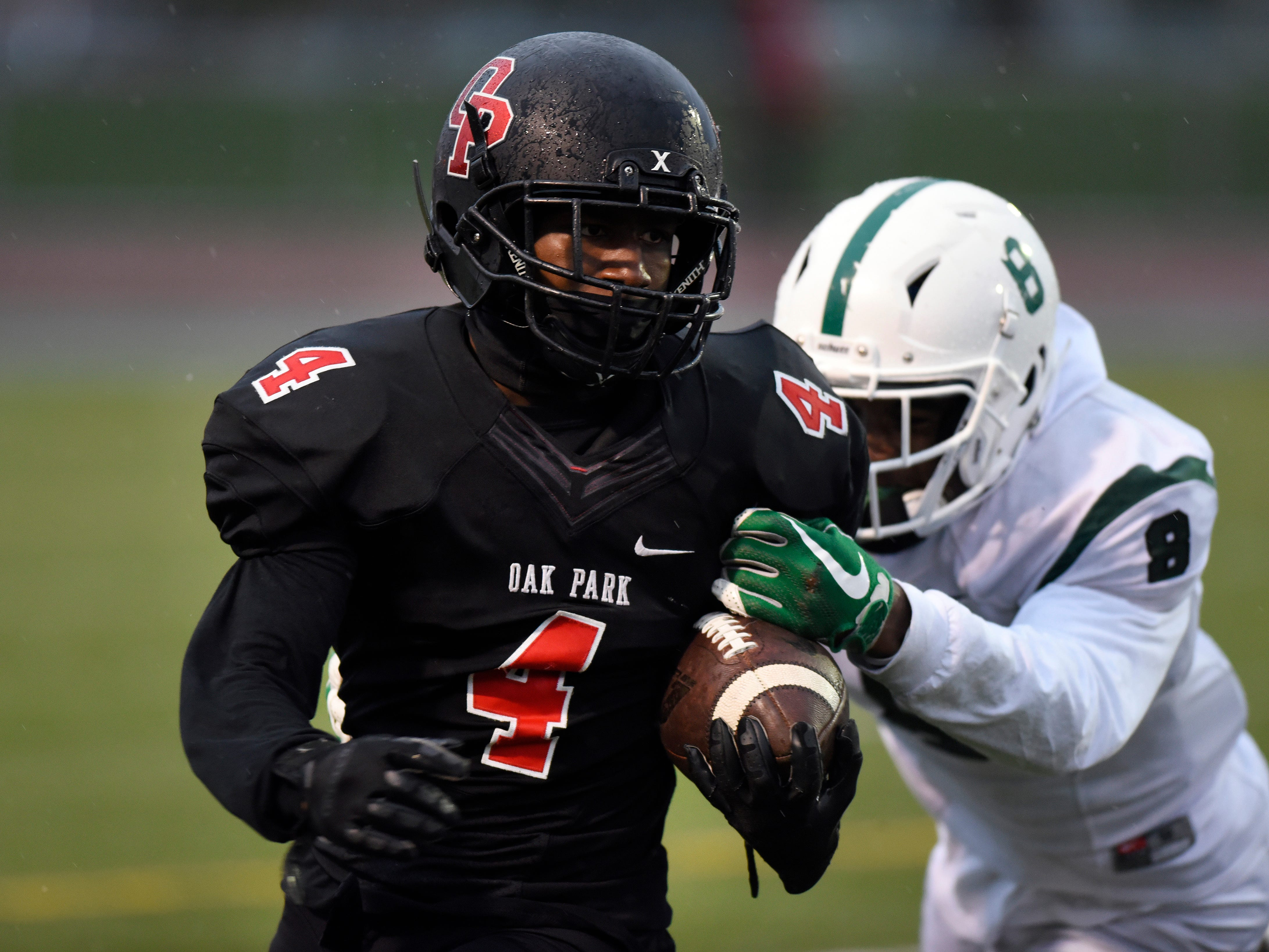 Oak Park running back Phillip Stewart (4) runs for yardage as he is tackled by West Bloomfield safety Makari Paige (8) during the first quarter.