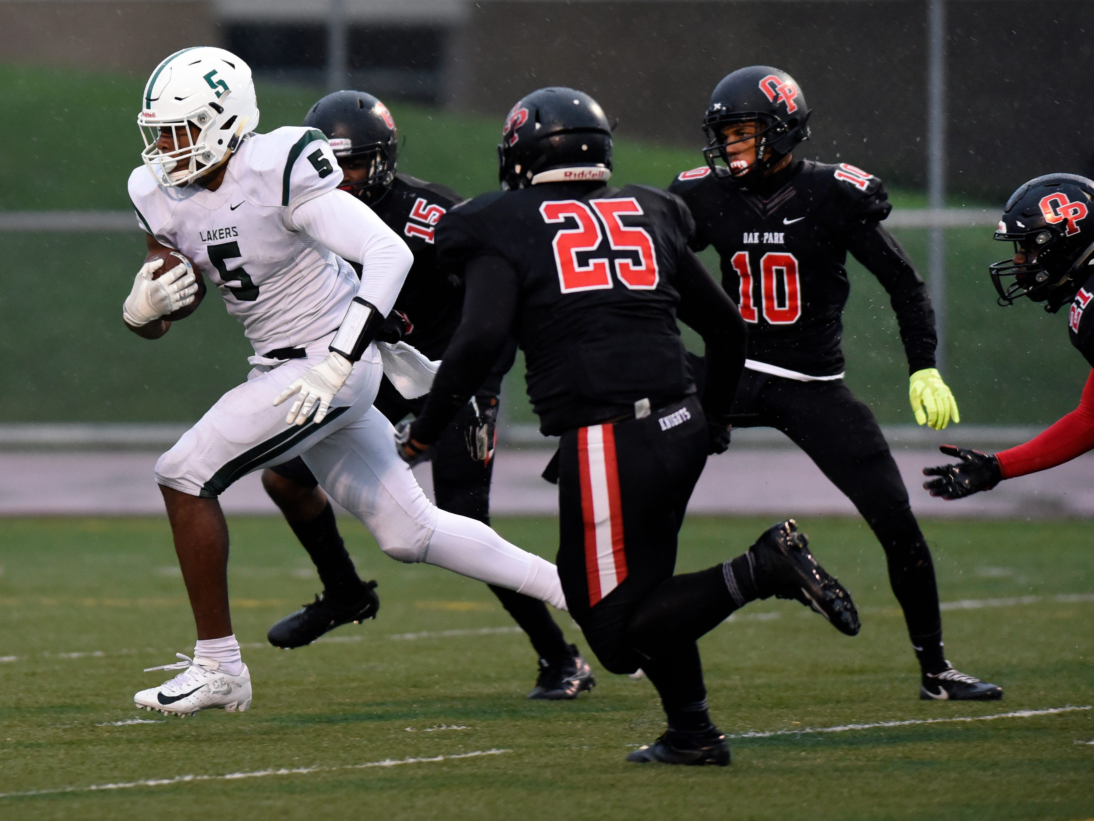 West Bloomfield running back Lance Dixon (5), left, runs for a touchdown past several Oak Park defenders during the first quarter.