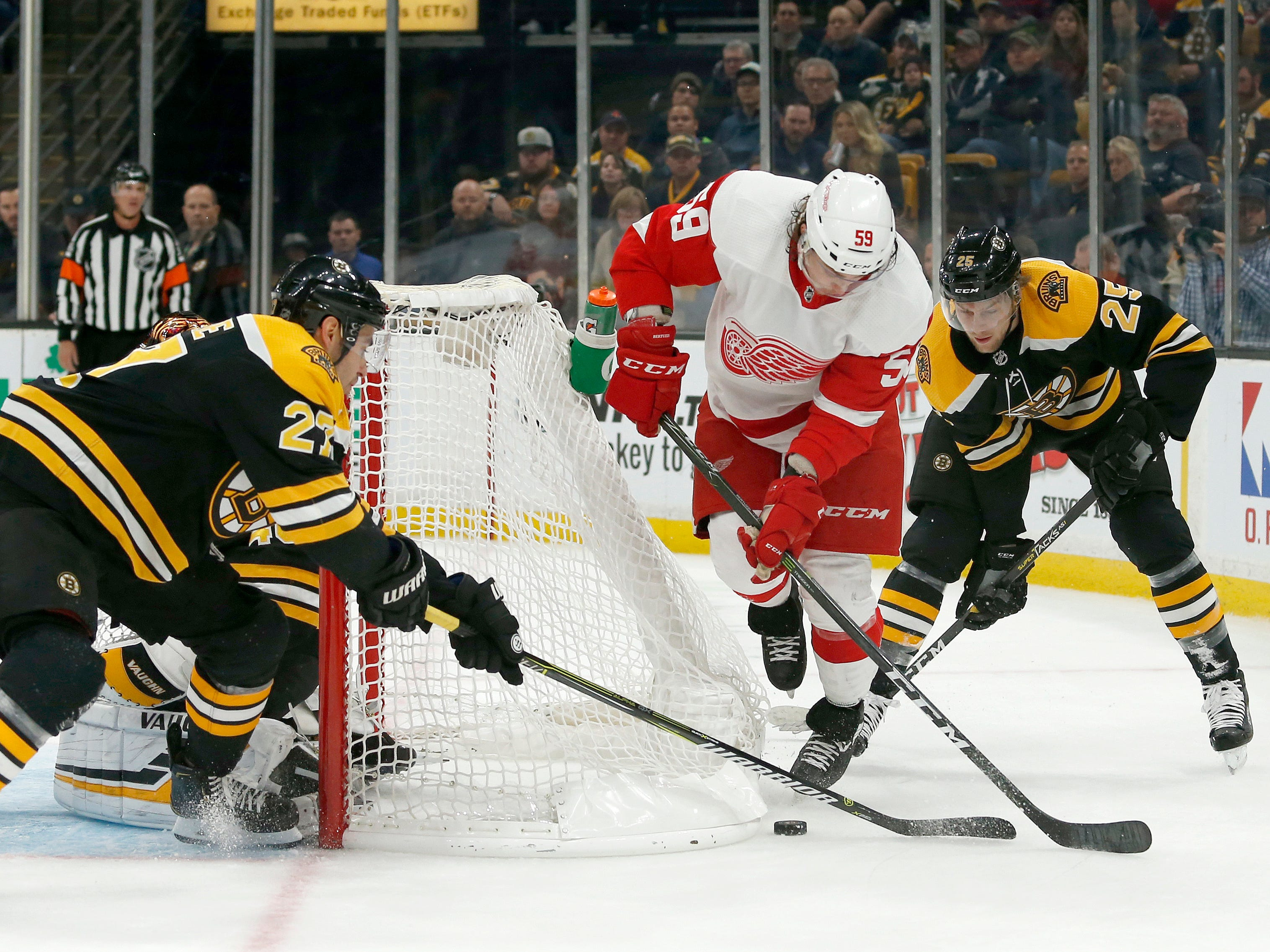 Detroit Red Wings left wing Tyler Bertuzzi (59) tries to move the puck around the net as Boston Bruins players John Moore (27) and Brandon Carlo (25) defend during the first period Saturday, Oct. 13, 2018, in Boston.