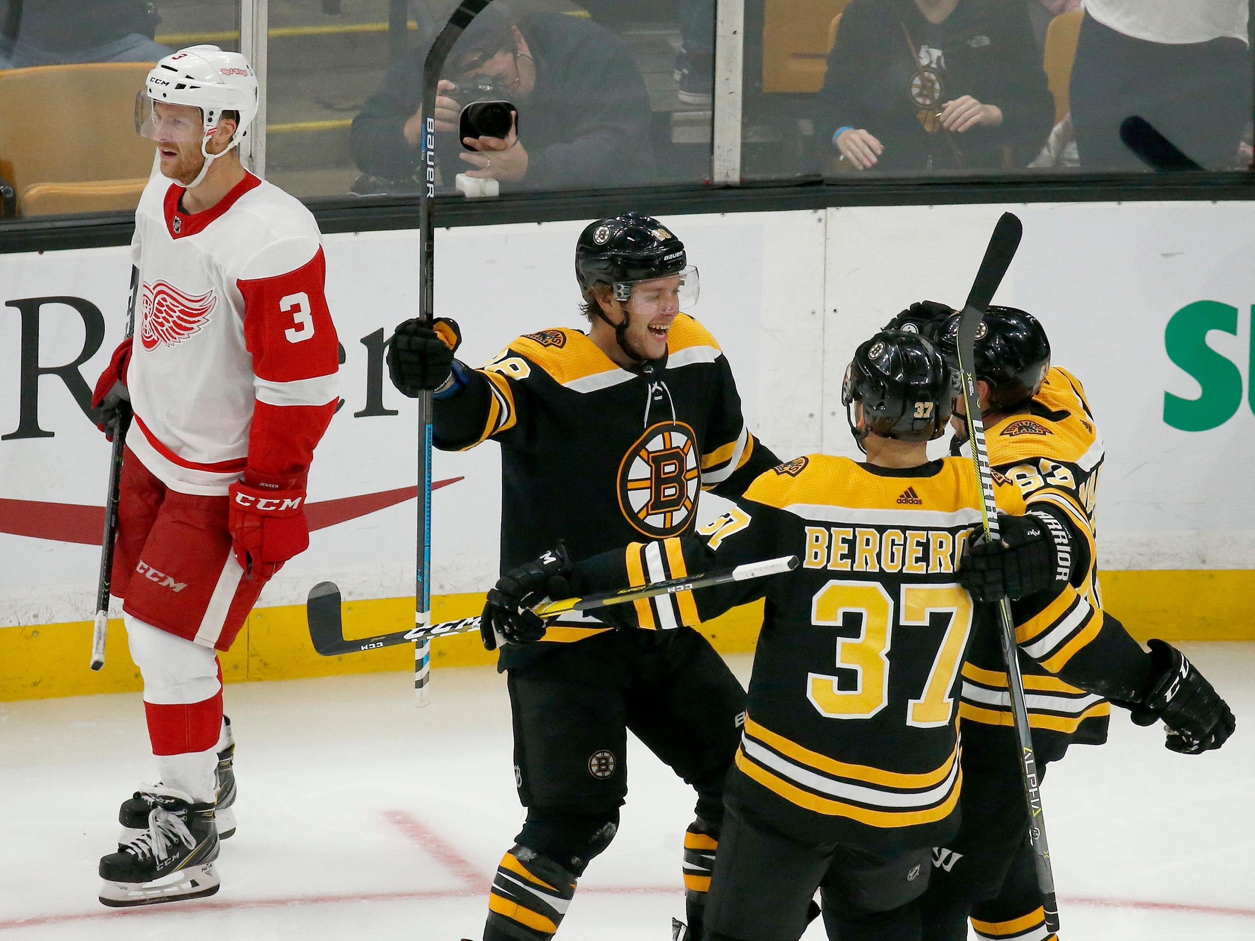 Boston Bruins right wing David Pastrnak celebrates his third goal of an NHL hockey game with teammates Patrice Bergeron (37) and Brad Marchand as Detroit Red Wings defenseman Nick Jensen (3) skates by during the third period.