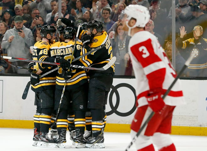 Boston Bruins players surround David Pastrnak after he scored as Detroit Red Wings defenseman Nick Jensen (3) looks up for the replay during the second period on Saturday.