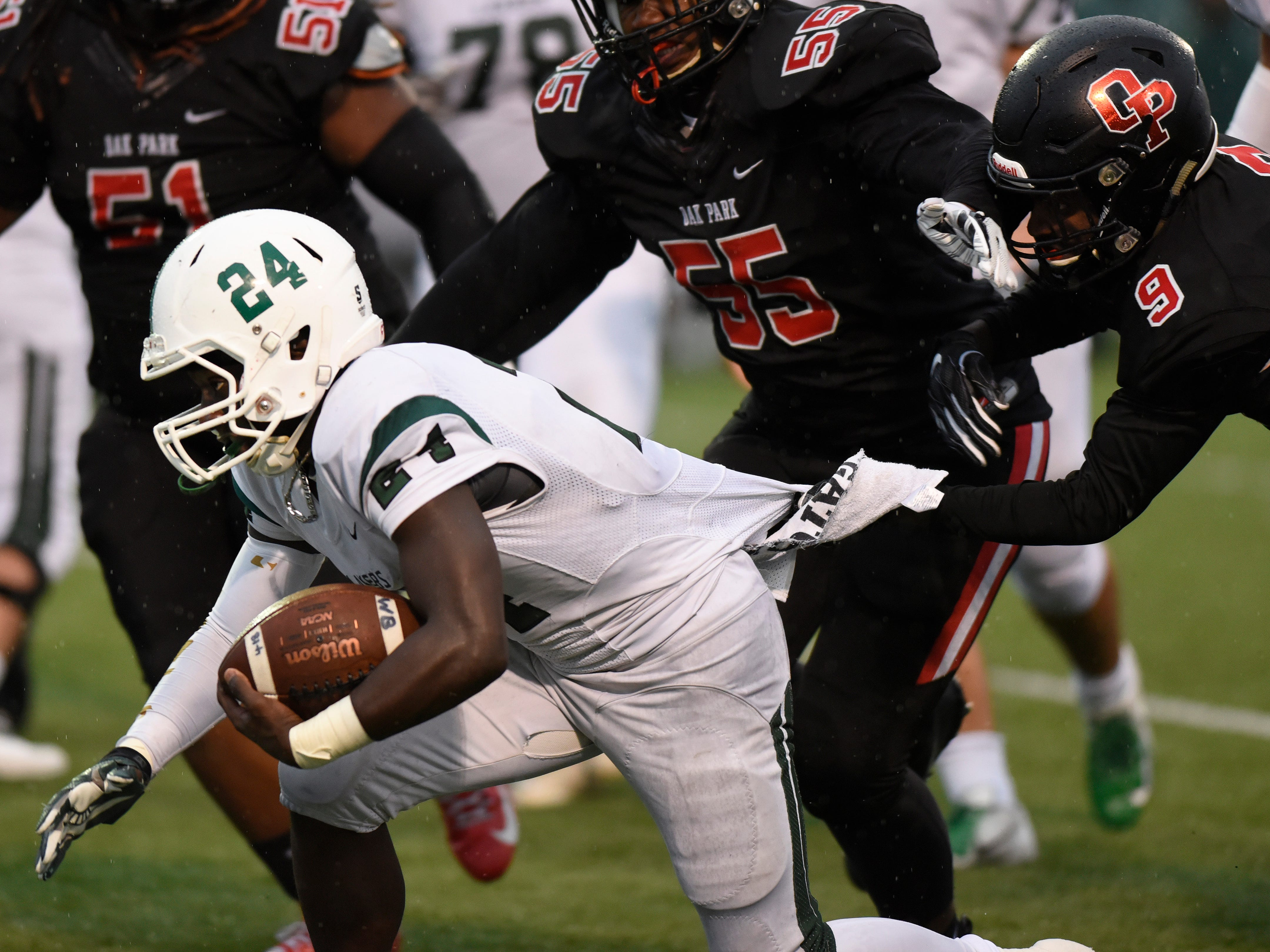 West Bloomfield running back Anthony May (24) runs for yardage and is tackled by Oak Park defender Corion Montgomery (9) during the first quarter.