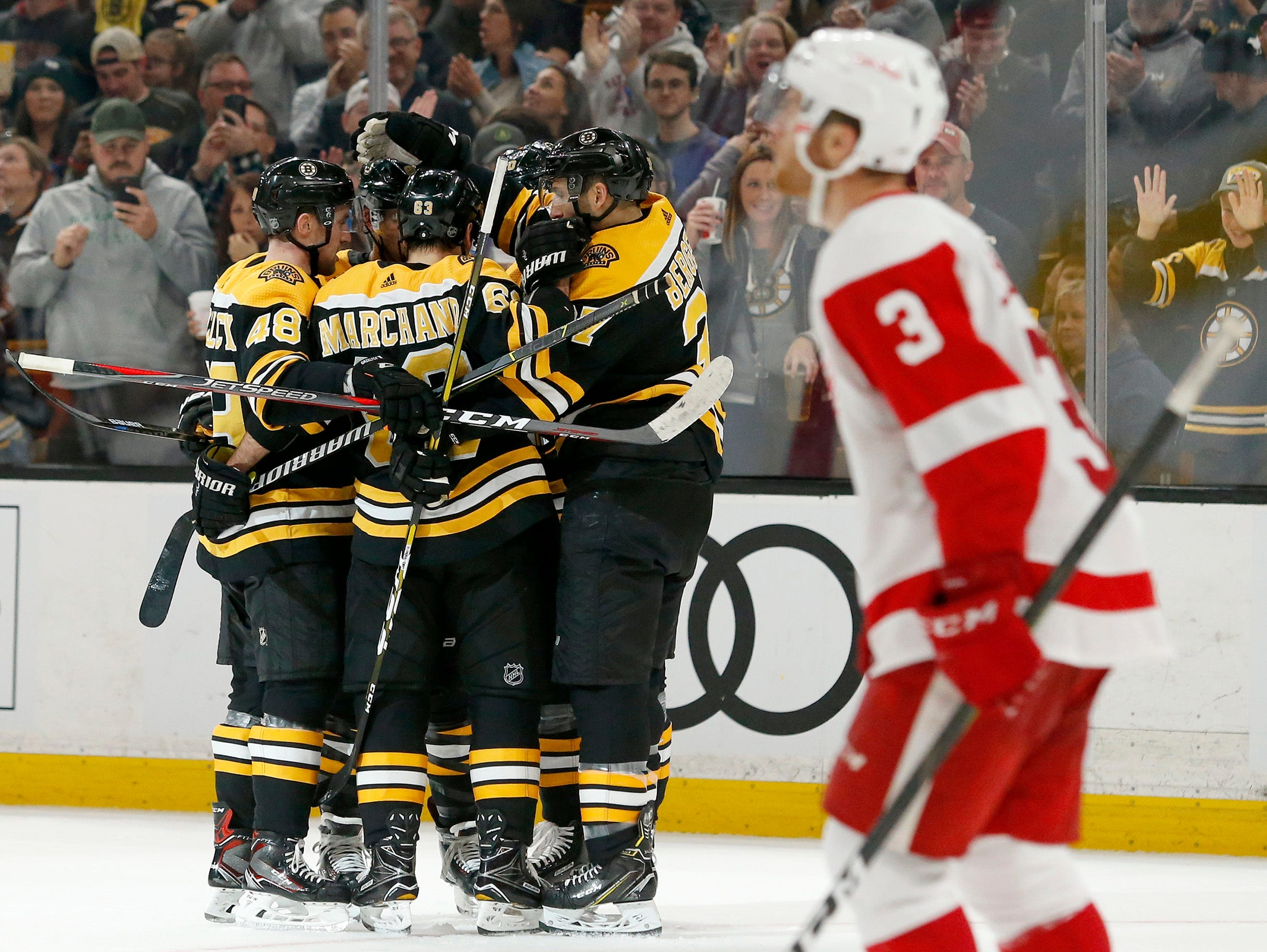 Boston Bruins players surround David Pastrnak after he scored as Detroit Red Wings defenseman Nick Jensen (3) looks up for the replay during the second period.