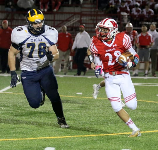 Thomas Price carries the ball for Waverly as Stephen Taylor of Tioga gives chase Oct. 12, 2018 at Waverly Memorial Stadium.