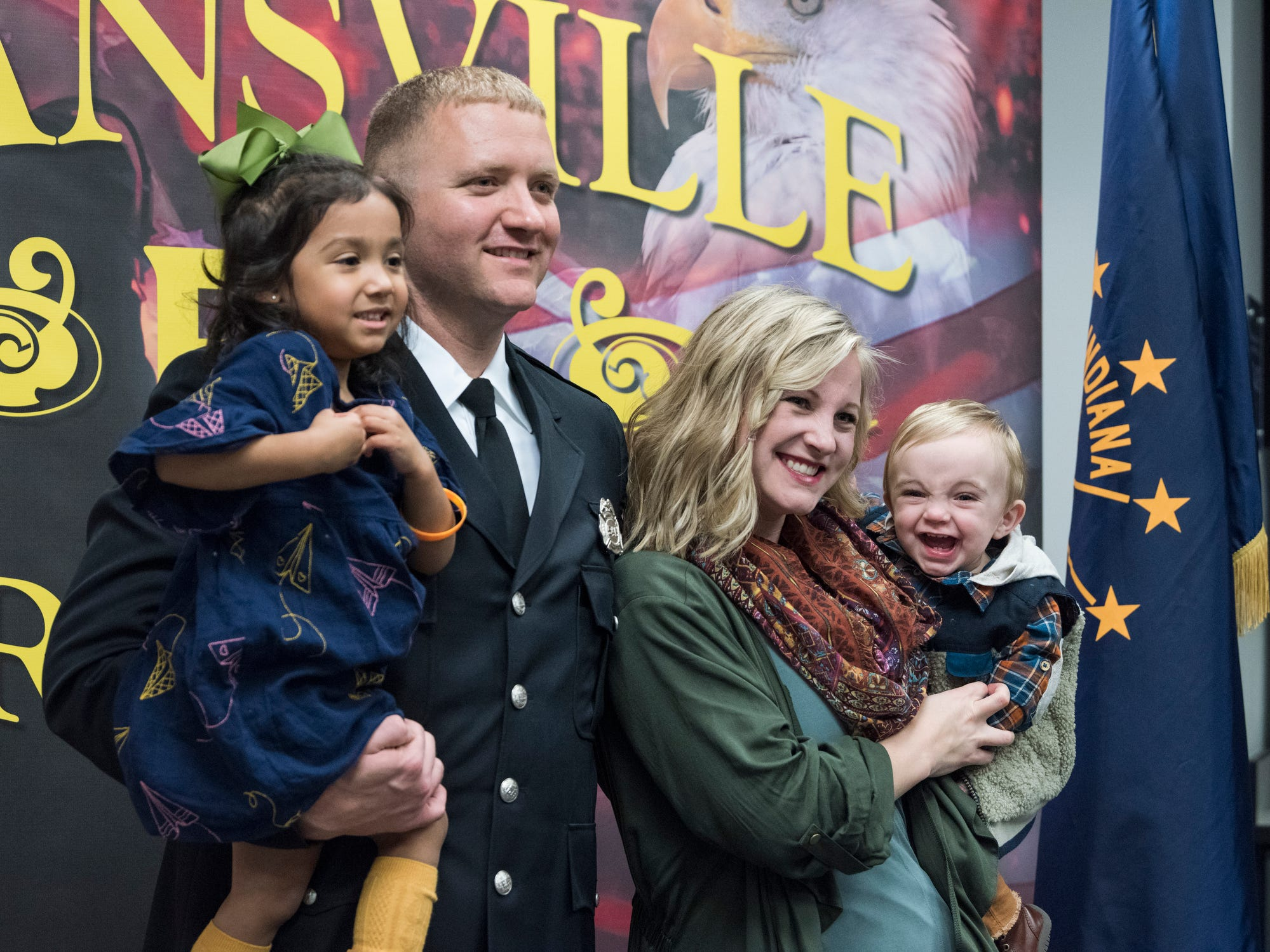 Michael Wilson poses for pictures with his wife and their children three-year-old Gracelyn, 3, and 10-month-old Elijah after his firefighter graduation ceremony at American Red Cross Headquarters in Evansville, Ind., Friday, Oct. 12, 2018.