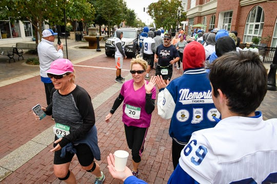 Marathoners run a gauntlet Memorial High School football players at the the Evansville Half Marathon Saturday morning, October 13, 2018.