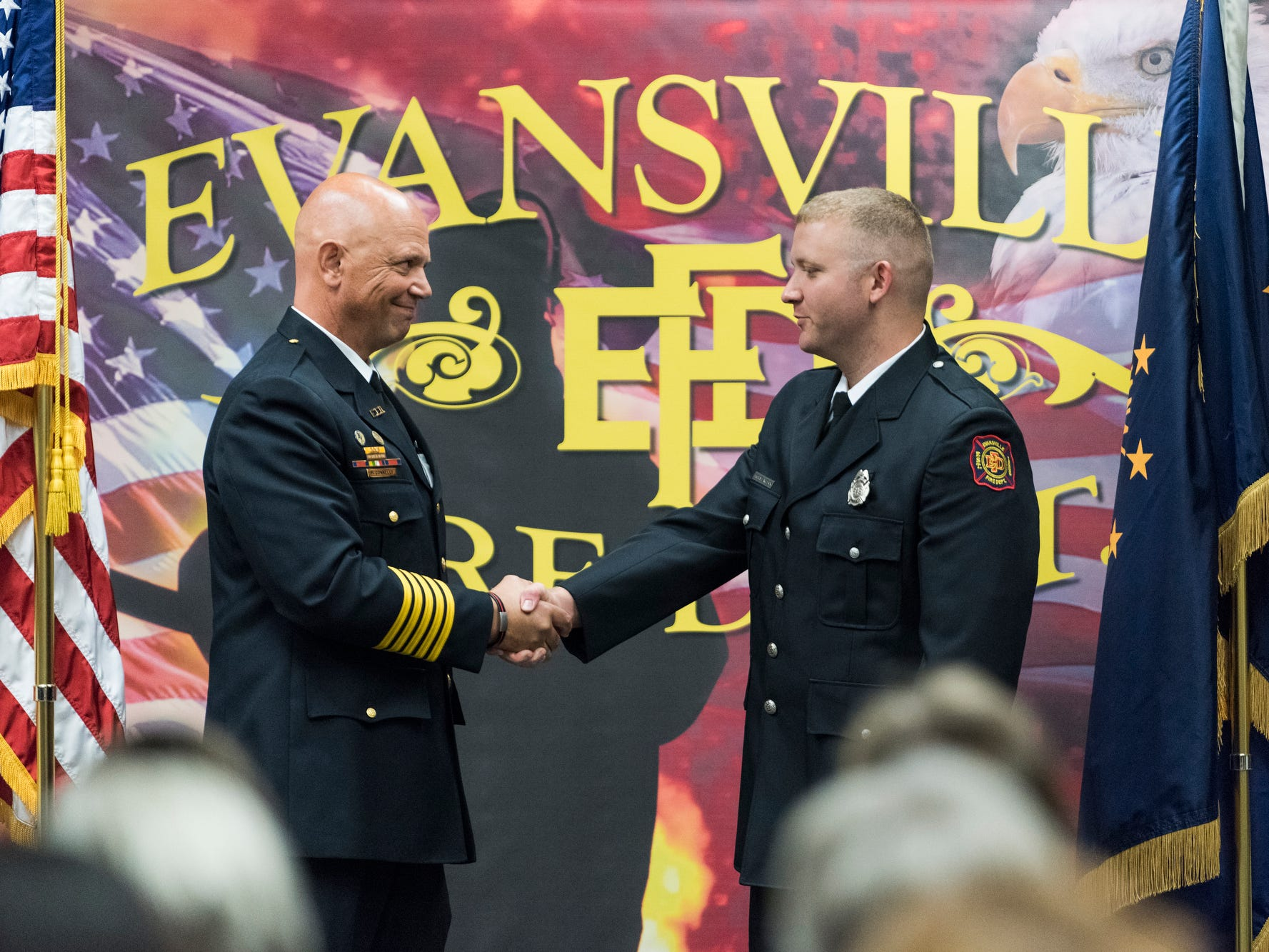 Evansville Fire Chief Charles Connolly, left, congratulates new probationary firefighter Michael Wilson, right, during his graduation ceremony at the American Red Cross Headquarters in Evansville, Ind., Friday, Oct. 12, 2018.
