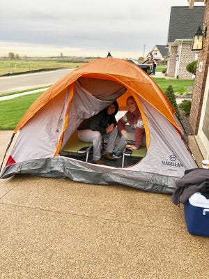 Stephanie and Sara Hatfield camp outside a model home in Newburgh Friday as they await the Saturday morning opening of the new Eastwick neighborhood where they plan to build a new home.