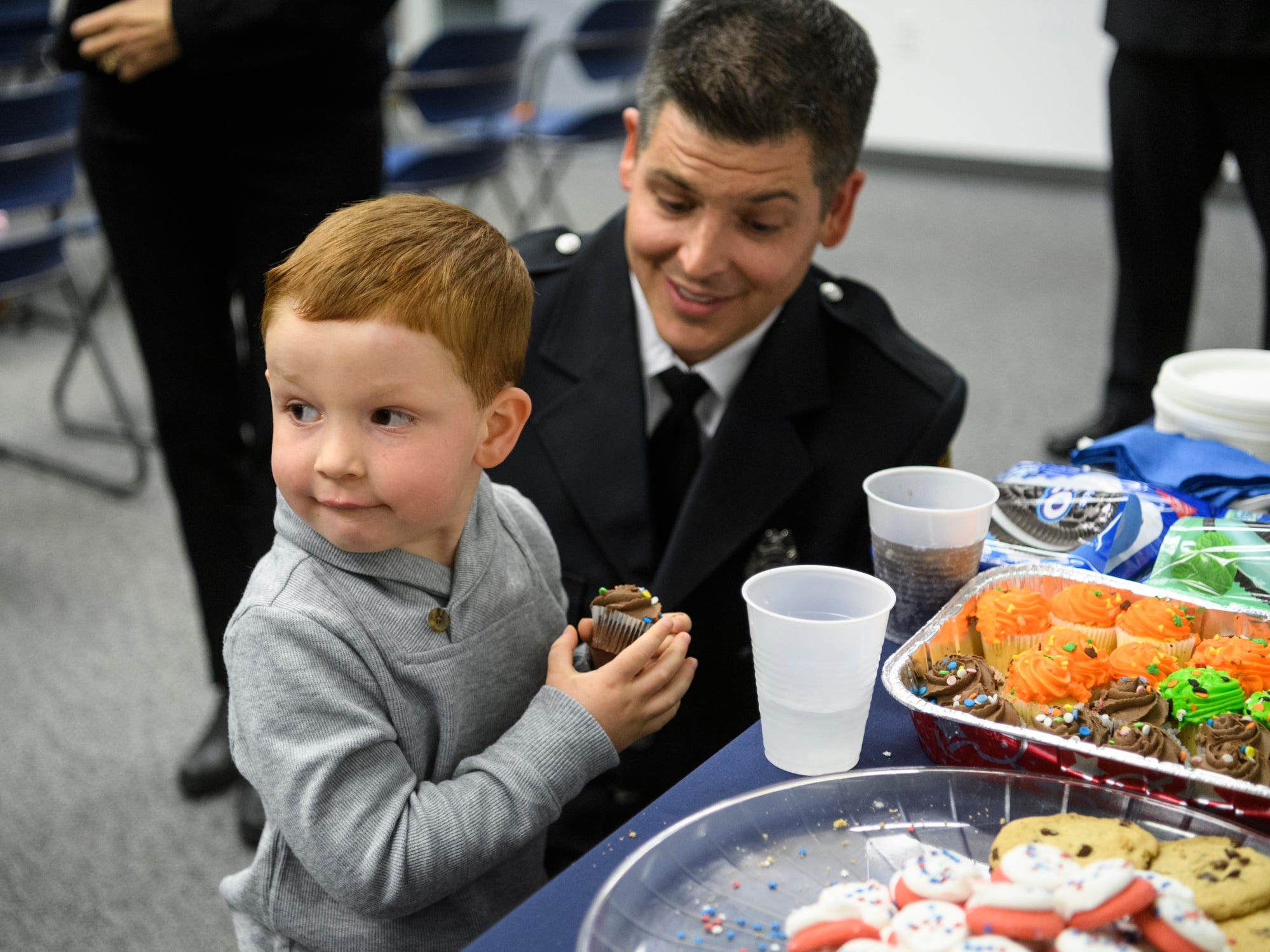Axel Harris, 4, grabs a cupcake from the graduation refreshment table as he spends time with his father Cameron Harris, a new probationary Evansville Firefighter, at the American Red Cross Headquarters in Evansville, Ind., Friday, Oct. 12, 2018.