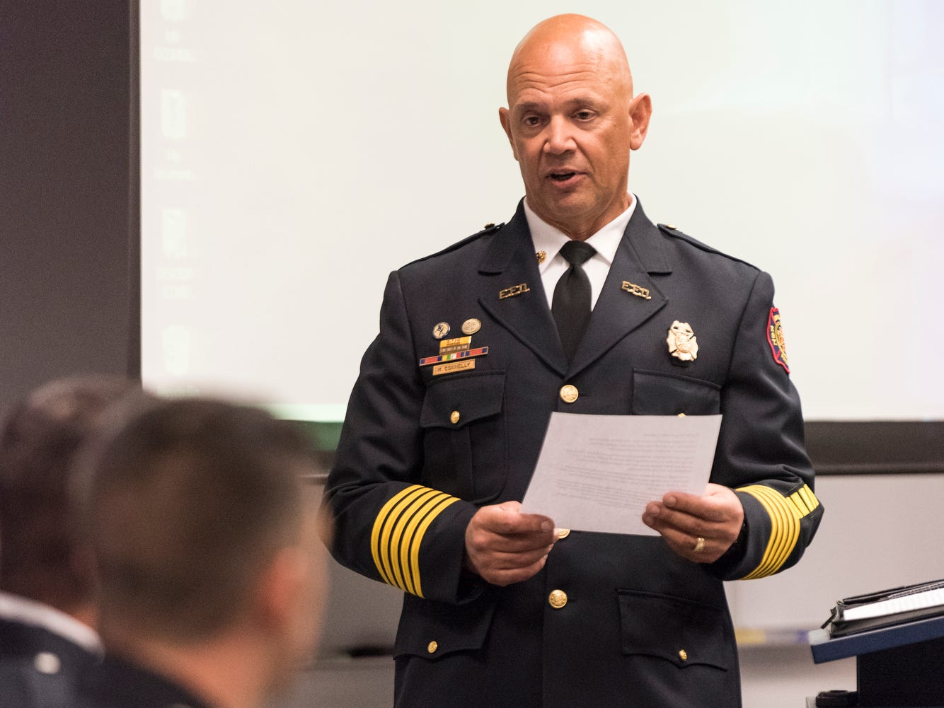Evansville Fire Chief Charles Connelly reads a statement from Mayor Lloyd Winnecke to the new probationary firefighters during their graduation ceremony at the American Red Cross Headquarters in Evansville, Ind., Friday, Oct. 12, 2018.