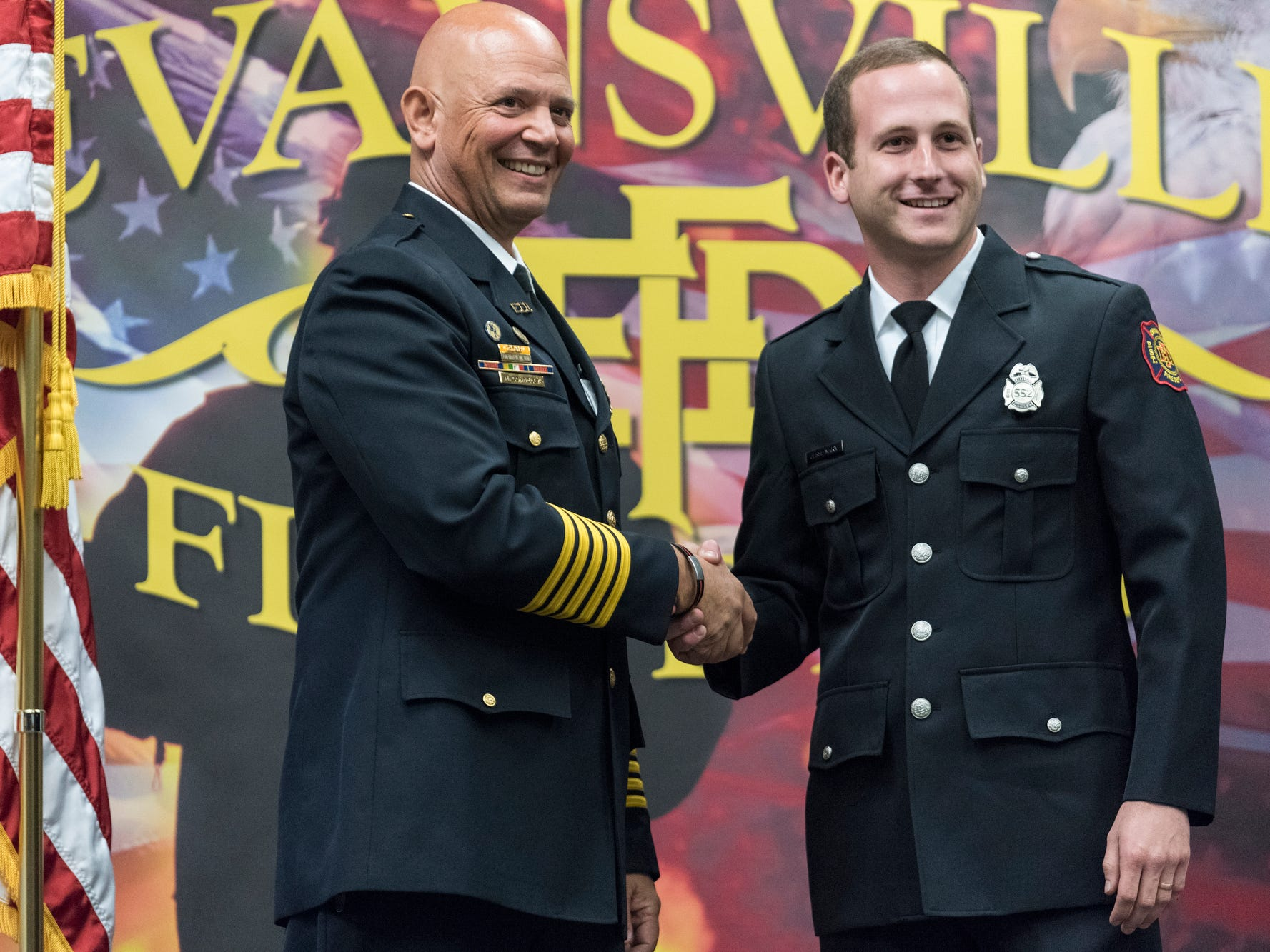 Evansville Fire Chief Charles Connolly, left, poses for a picture with new probationary firefighter Jesse Marx, right, during his graduation ceremony at the American Red Cross Headquarters in Evansville, Ind., Friday, Oct. 12, 2018.