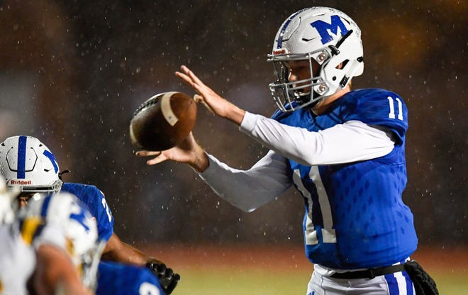Memorial quarterback Michael Lindauer (11) takes a snap in the rain as the Memorial Tigers play the Castle Knights at Evansville's Enlow Field Friday, October 12, 2018.