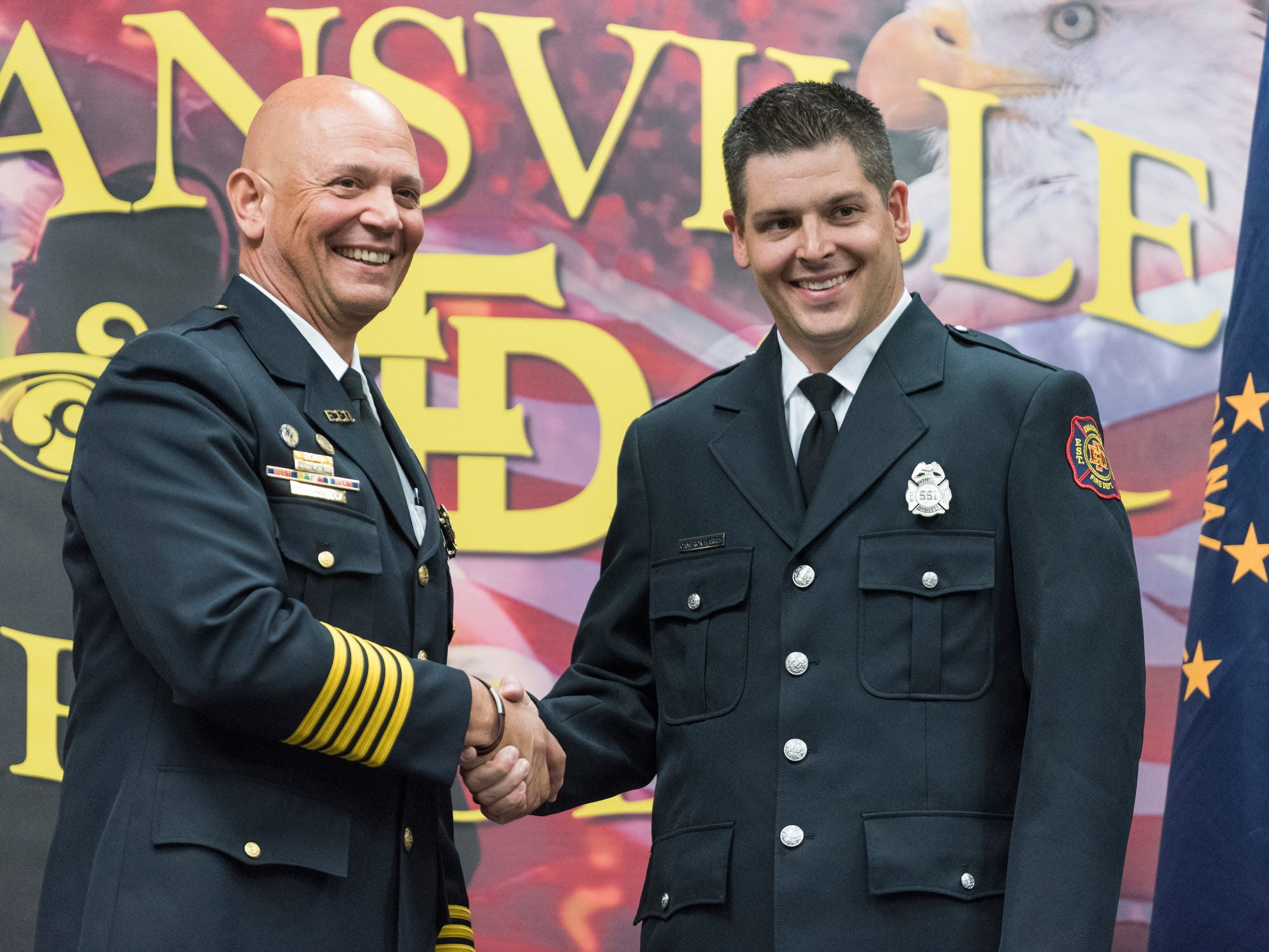 Evansville Fire Chief Charles Connolly, left, poses for a picture with new probationary firefighter Cameron Harris, right, during his graduation ceremony at the American Red Cross Headquarters in Evansville, Ind., Friday, Oct. 12, 2018.