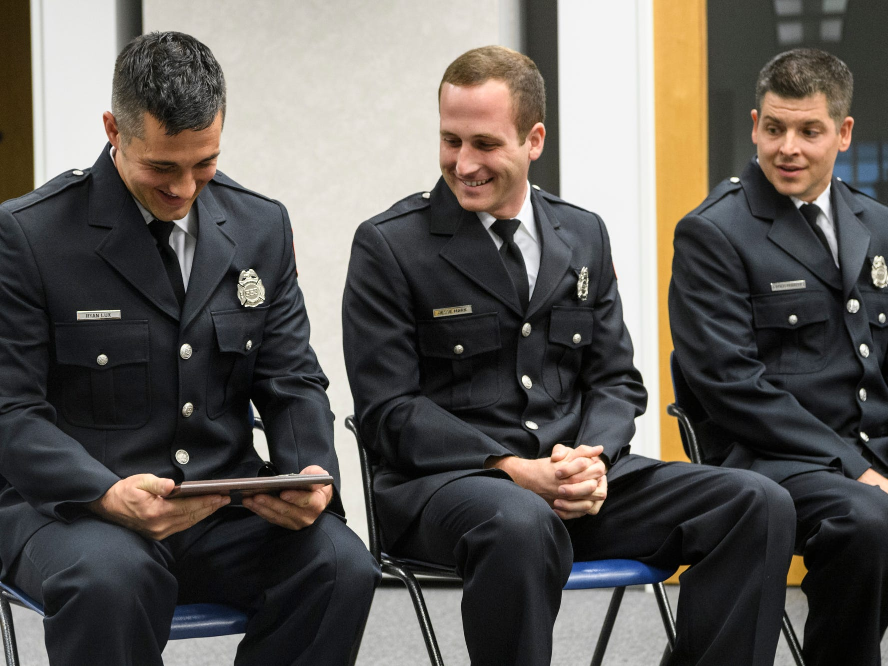 Ryan Lux, from left, looks at his Distinguished Recruit plaque as fellow firefighter graduates Jesse Marx and Cameron Harris sit next to him during their graduation ceremony at the American Red Cross Headquarters in Evansville, Ind., Friday, Oct. 12, 2018.