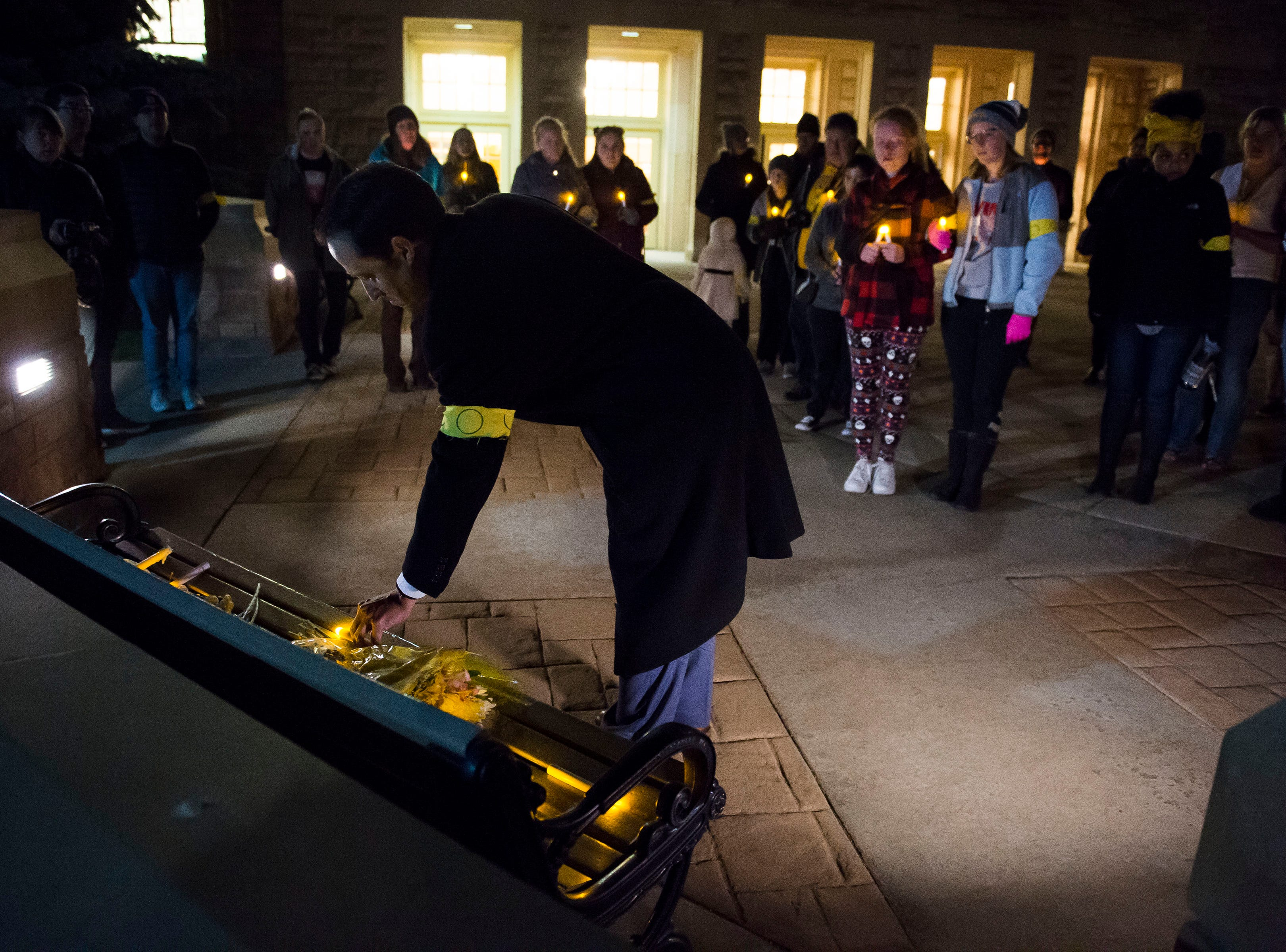 University of Wyoming chief of staff Dan Maxey sets his flameless candle down on a bench dedicated to Matthew Shepard after a candlelight vigil on the 20th anniversary of Shepard's death on Friday, Oct. 12, 2018, at Prexy's Pasture on the University of Wyoming campus in Laramie, Wyo.